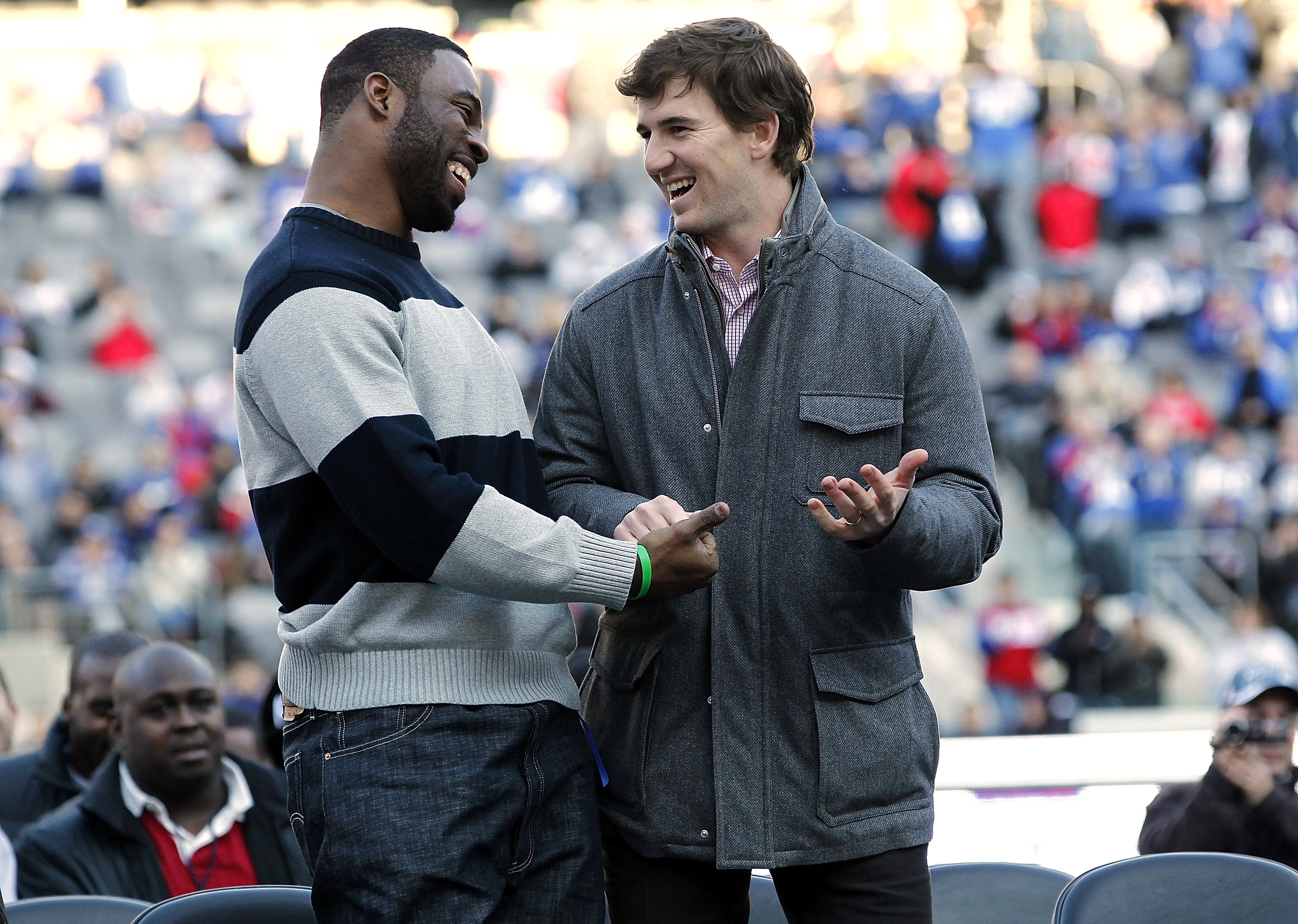 Justin Tuck (L) laughs with teammate Eli Manning at a rally to celebrate the New York Giants' event