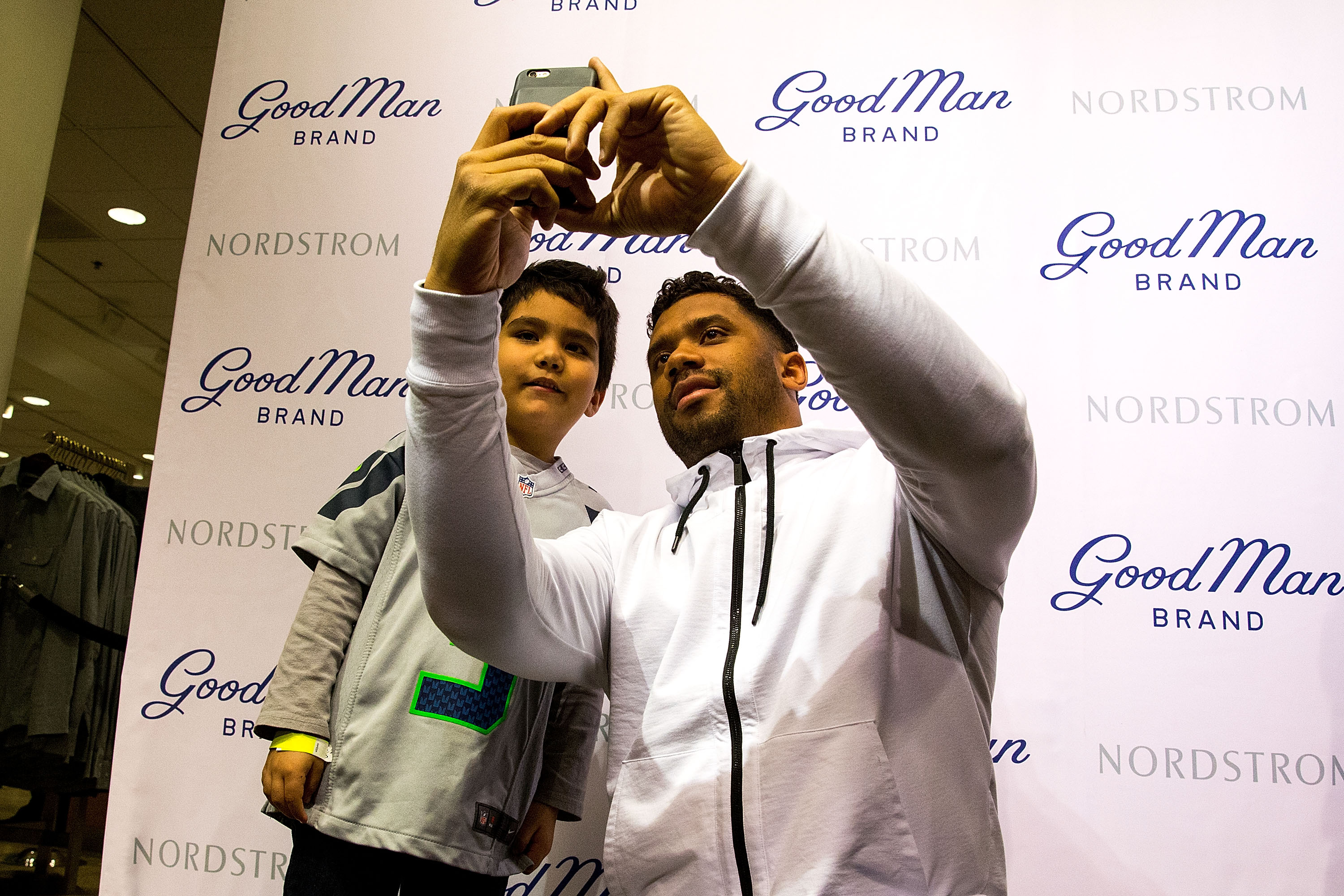 Seattle Seahawks quarterback Russell Wilson poses for a selfie with a fan at Nordstrom during his Good Man Brand clothing line launch