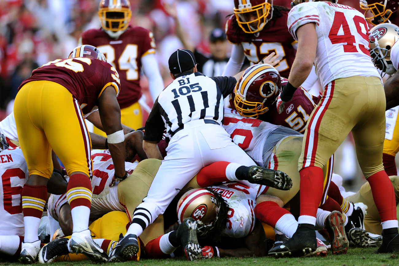 What happens at the bottom of an NFL pile after a fumble?