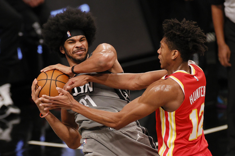 Jarrett Allen of the Brooklyn Nets fights De'Andre Hunter of the Atlanta Hawks for the ball