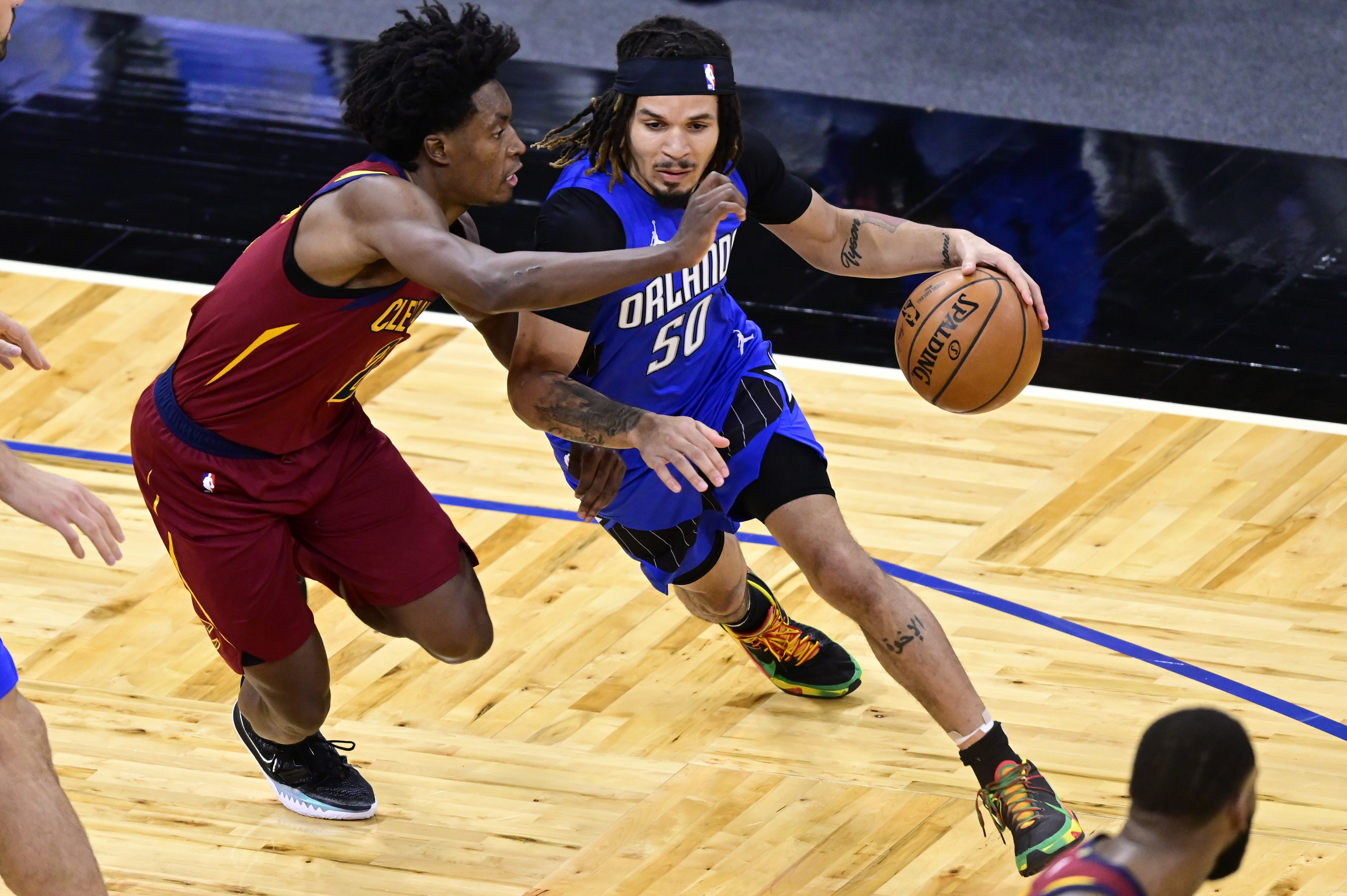 Cole Anthony of the Orlando Magic dribbles the ball as Collin Sexton of the Cleveland Cavaliers defends