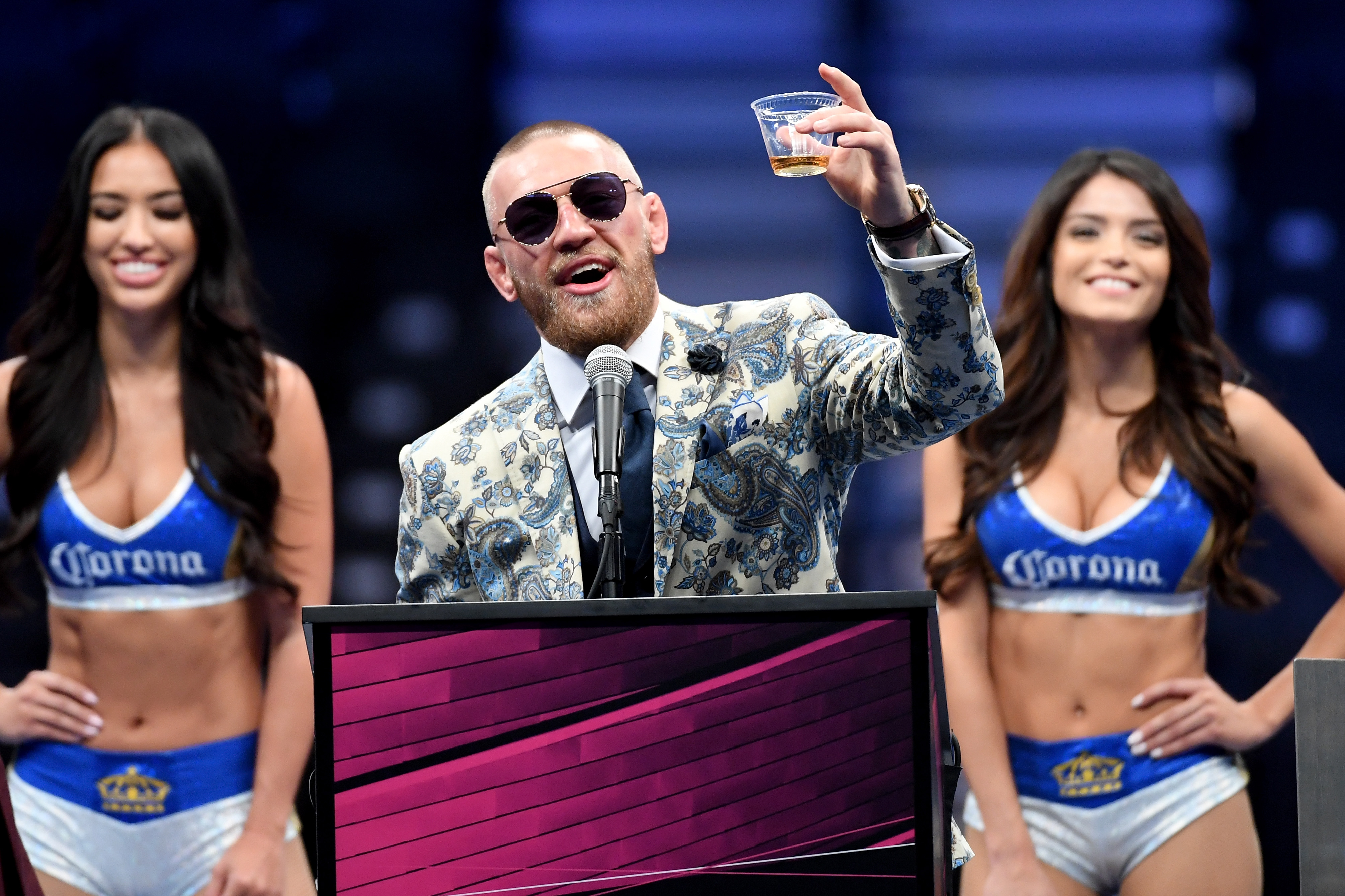 Conor McGregor holds up a cup of his Notorious-branded Irish whiskey