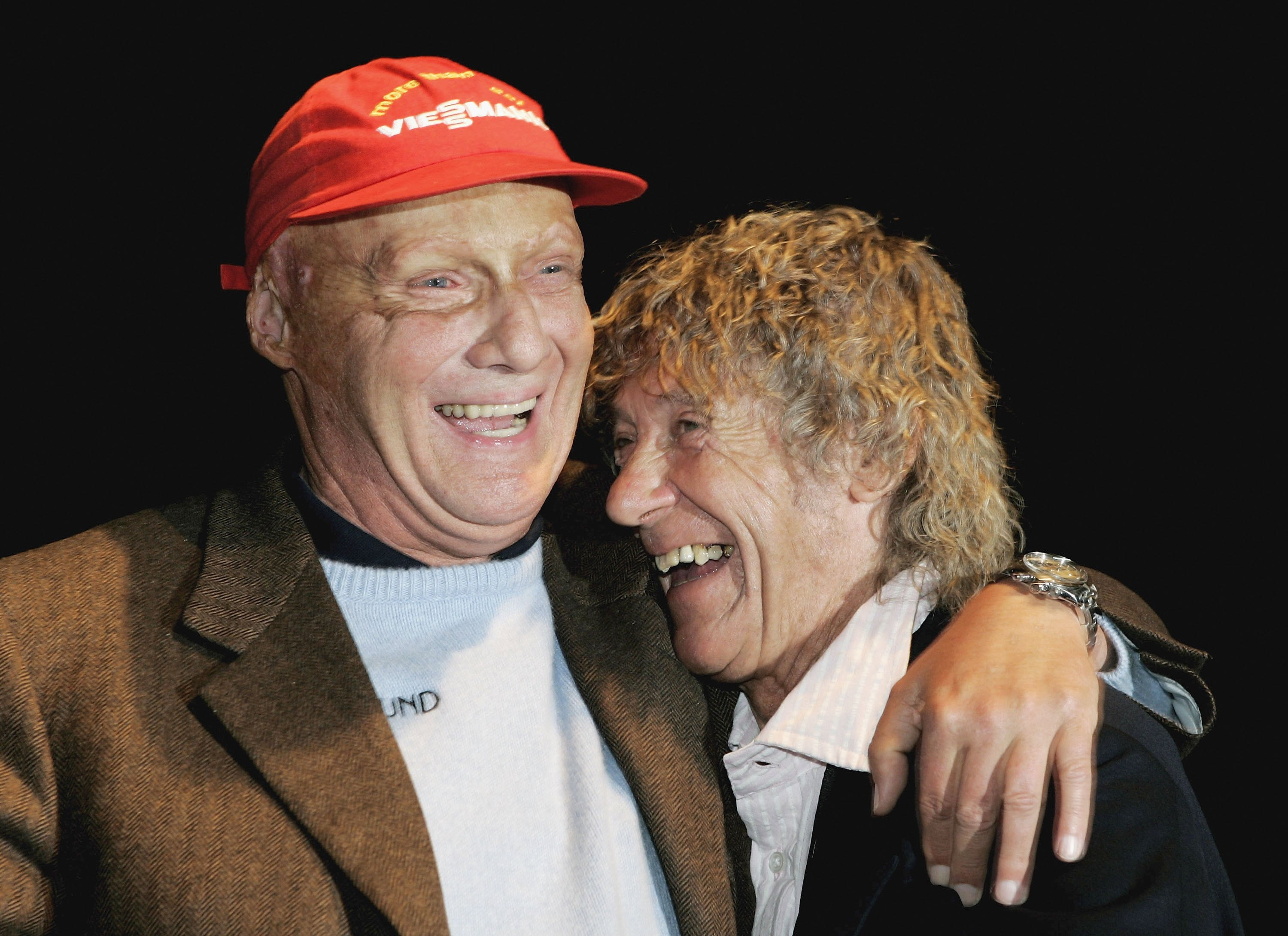Former Formula One drivers Niki Lauda (L) and Arturo Mezario laugh during the 2006 Motorsport Traveling Charity-Gala