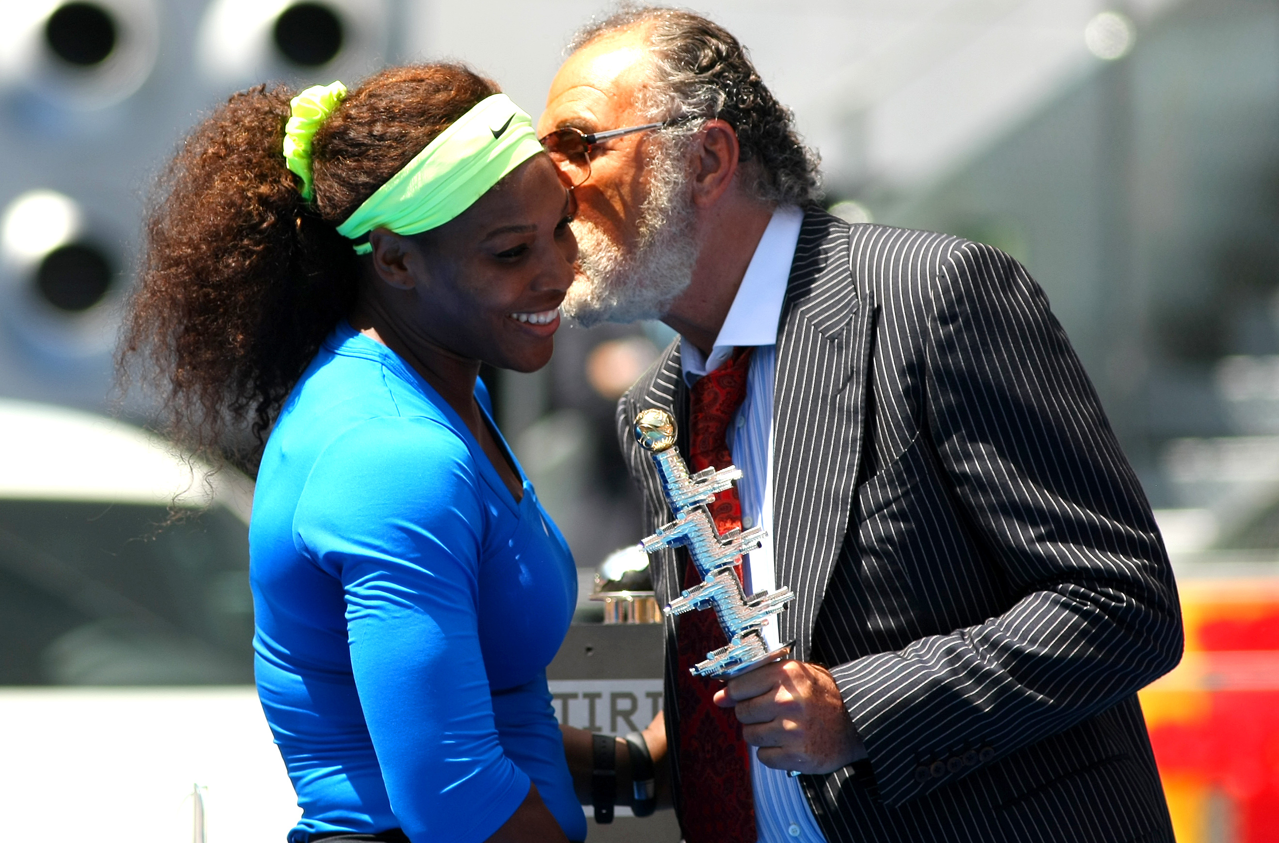 Serena Willams receives a kiss and the trophy from Ion Tiriac following her 2012 win in Madrid