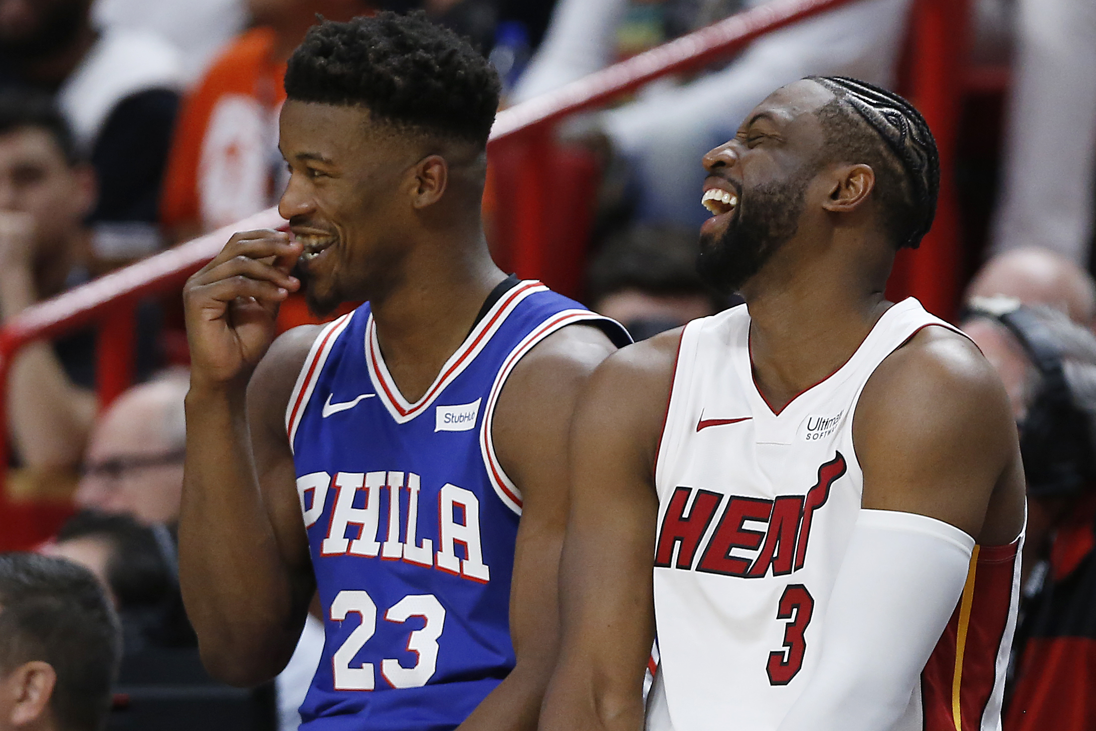 Dwyane Wade and Jimmy Butler laugh while waiting to check into a game