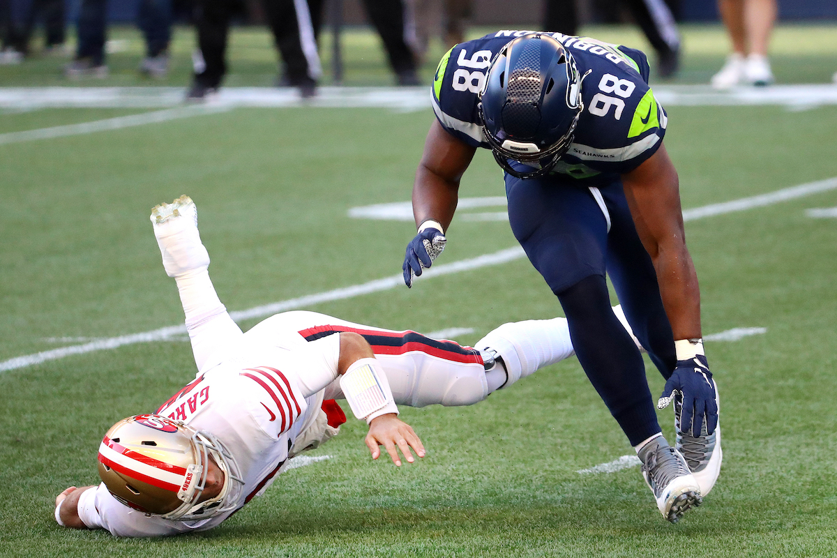 Jimmy Garoppolo (left) of the San Francisco 49ers is tackled by Alton Robinson of the Seattle Seahawks in the second quarter at CenturyLink Field on November 1, 2020, in Seattle, Washington.