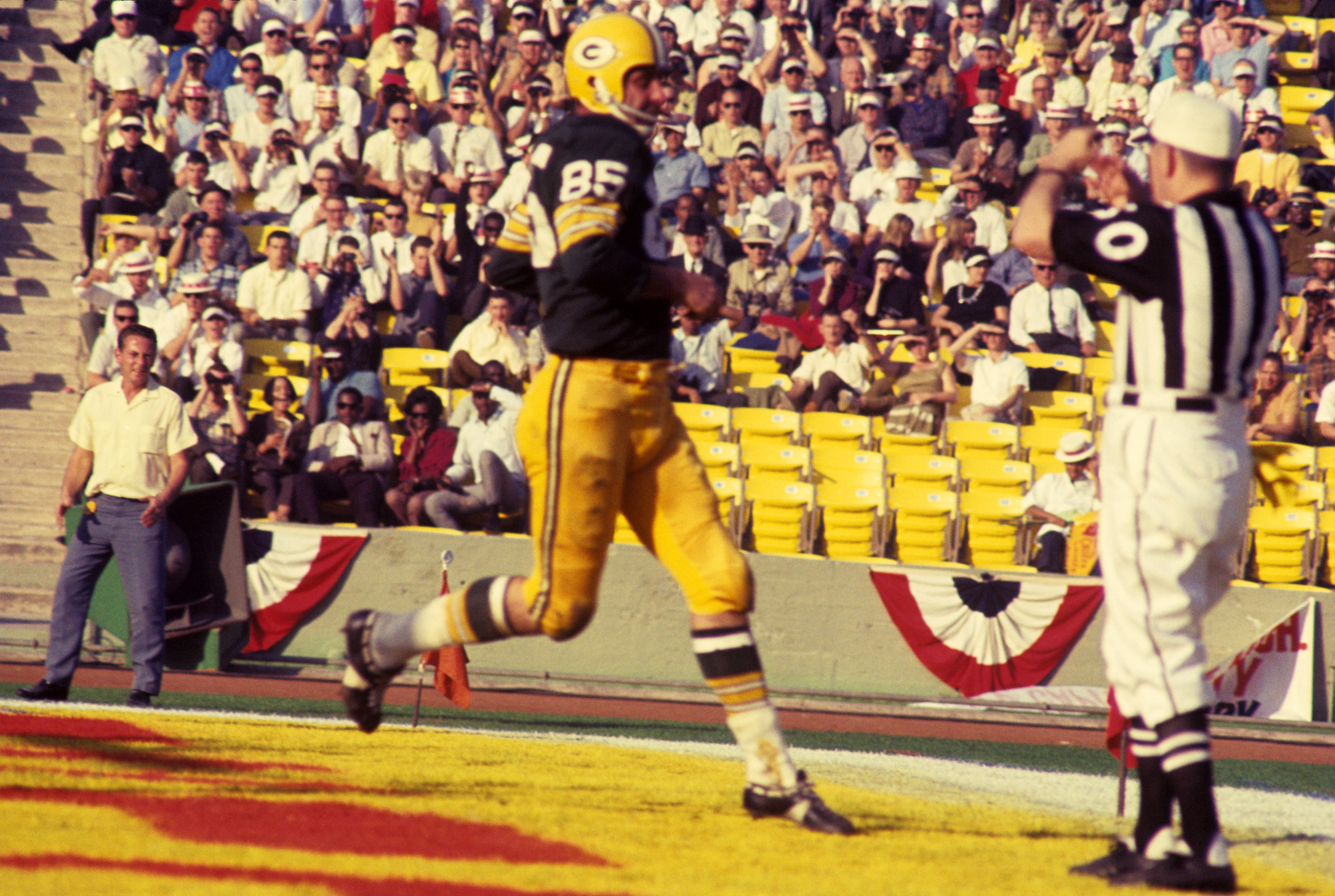 Wide receiver Max McGee, #85 of the Green Bay Packers, scores on a 13-yard touchdown pass from quarterback Bart Starr in the third quarter of Super Bowl I on January 15, 1967, against the Kansas City Chiefs at the Los Angeles Memorial Coliseum in Los Angeles, California.