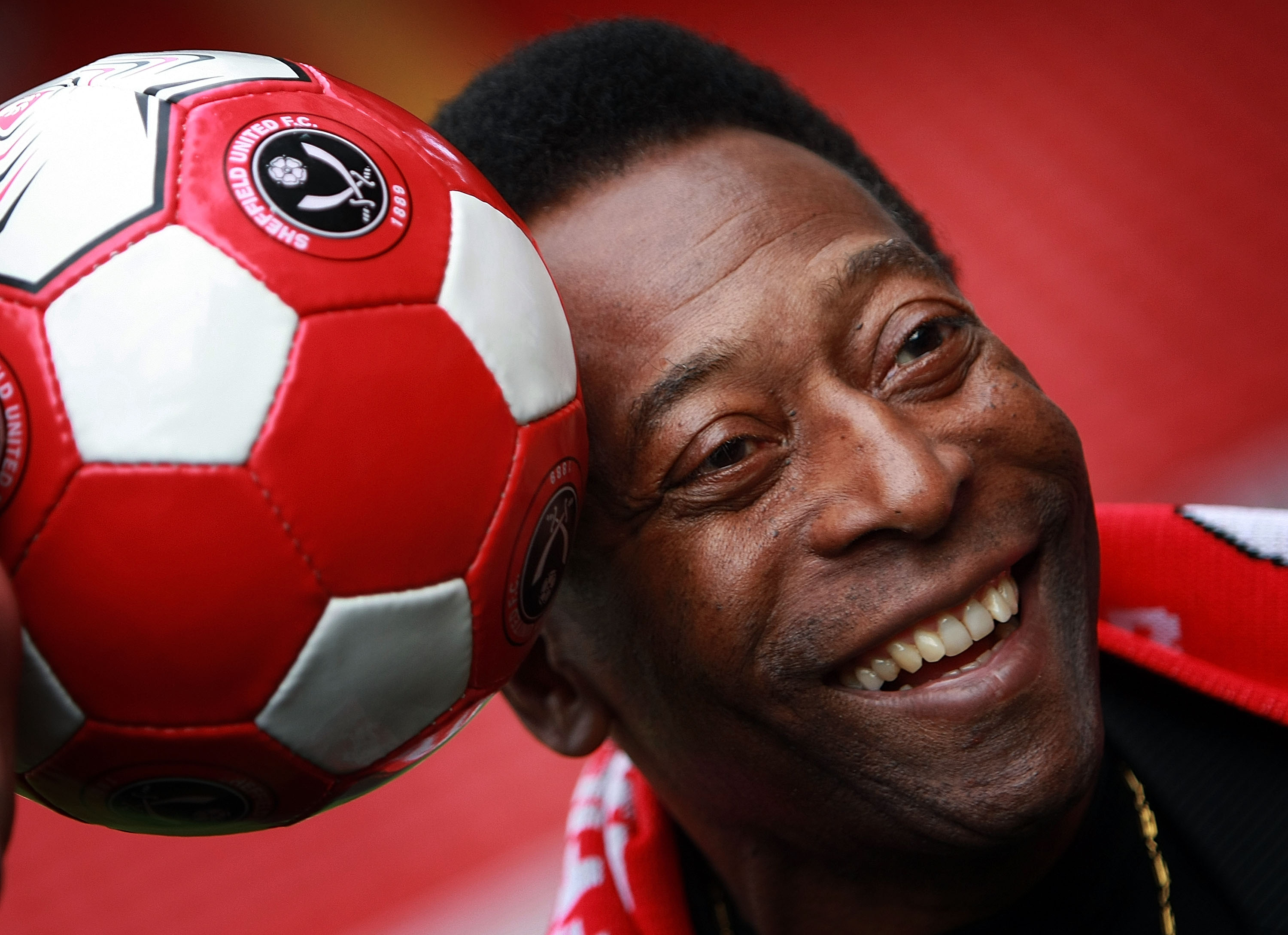 Pelé rests his head on a soccer ball for a picture
