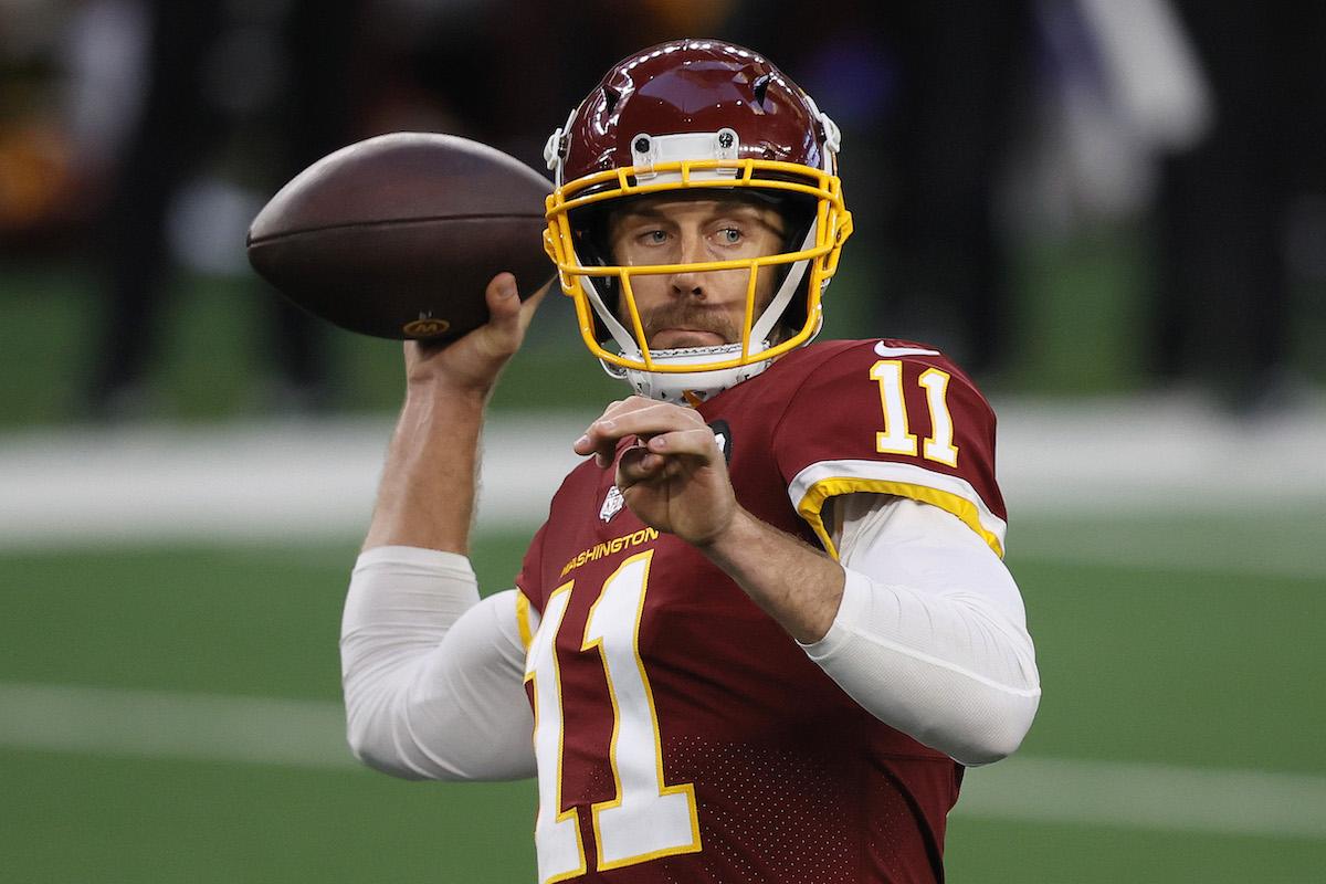Alex Smith of the Washington Football Team surveys the field to throw the ball