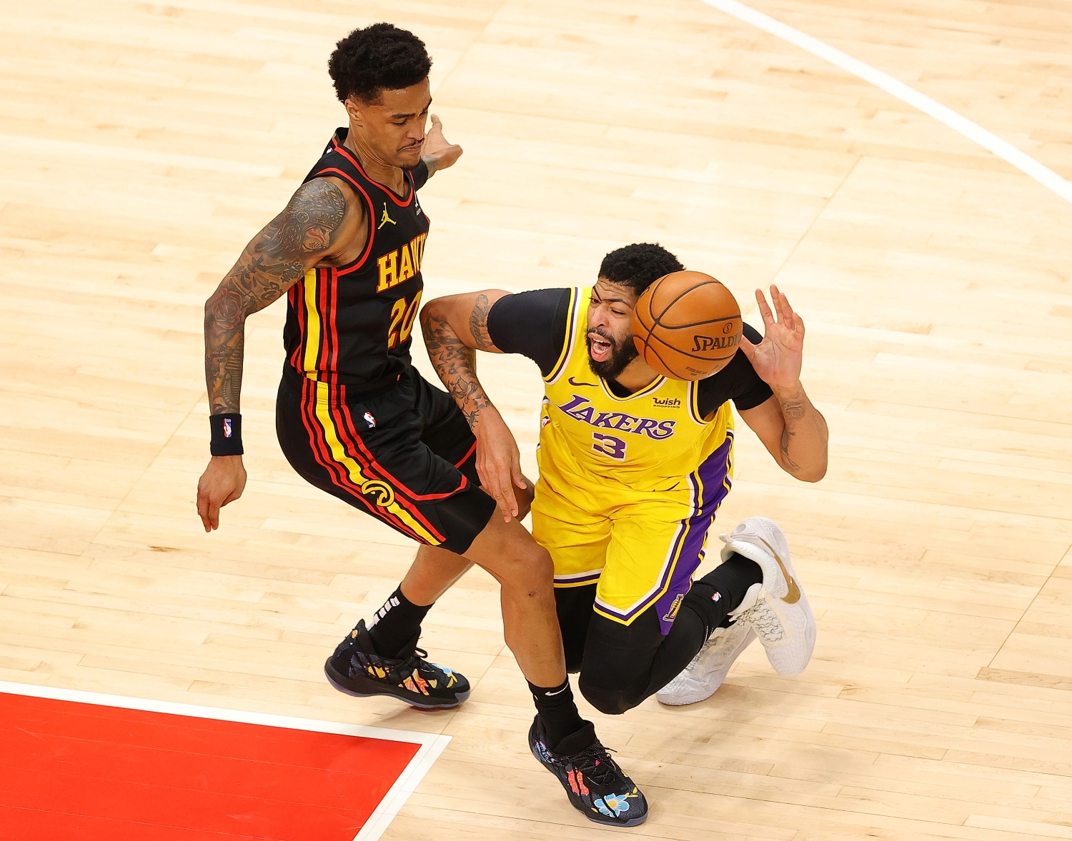 Anthony Davis of the Los Angeles Lakers draws a foul as he falls the court against John Collins of the Atlanta Hawks.