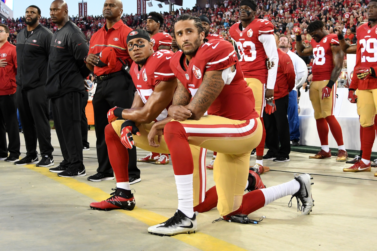 Colin Kaepernick kneels during the National Anthem with his teammate