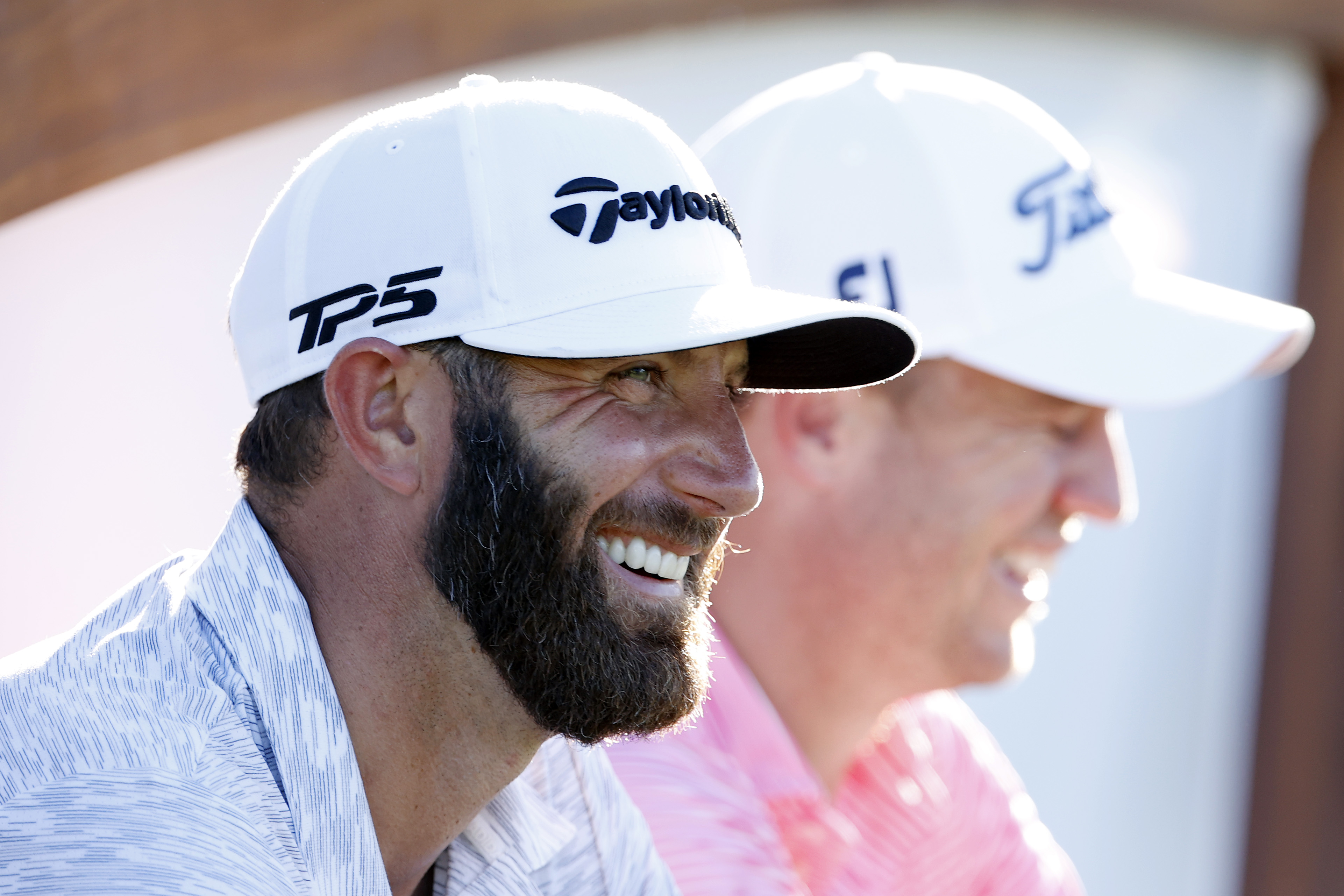 Dustin Johnson laughs as they wait on the 18th tee during the 2021 Sentry Tournament Of Champions