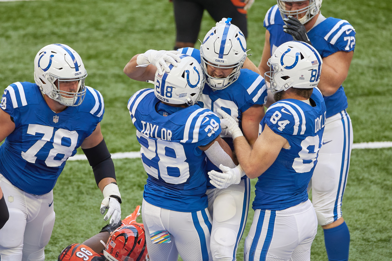 Colts players Trey Burton, Jonathan Taylor, and Jack Doyle celebrate against the Bengals.