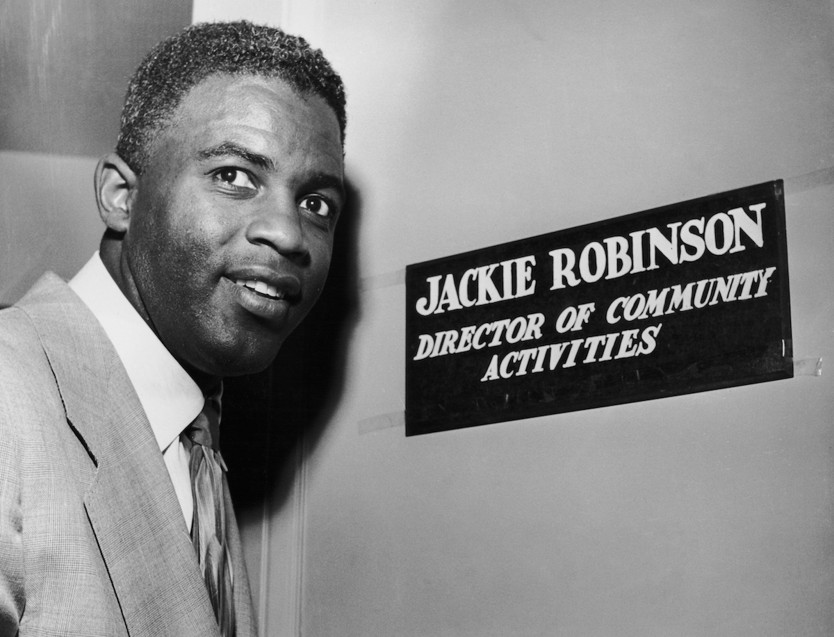 Jackie Robinson smiles by his door that is for his new job at WNBC