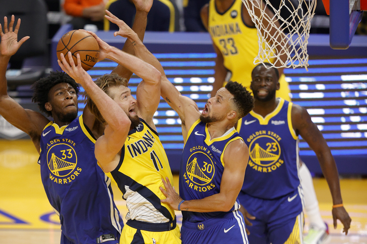 James Wiseman and Stephen Curry of the Warriors defend a Domantas Sabonis shot against the Pacers.