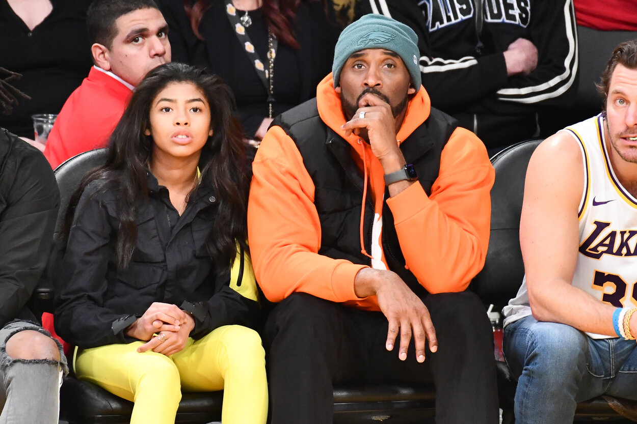 Los Angeles Lakers legend Kobe Bryant and his daughter, Gianna, sit at a basketball game in 2019.