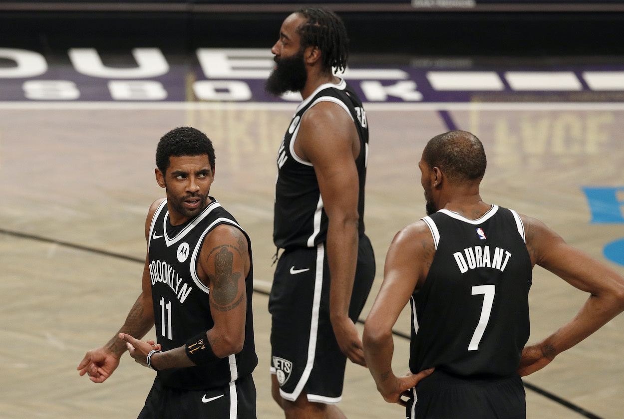 Kyrie Irving, James Harden, and Kevin Durant of the Brooklyn Nets talk during a game against the Miami Heat