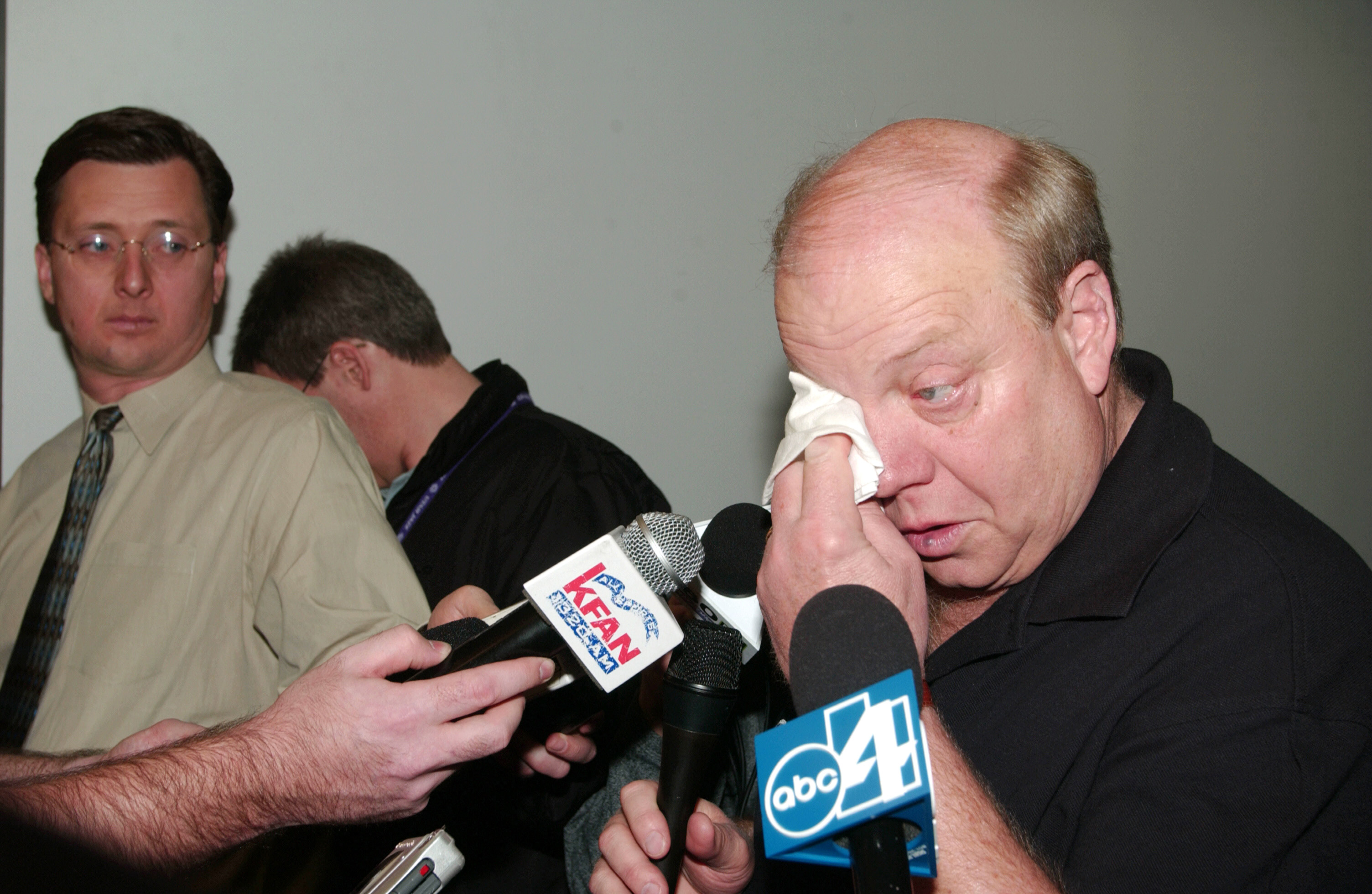 Larry H. Miller of the Utah Jazz wipes away a tear as he speaks to the media in 2003