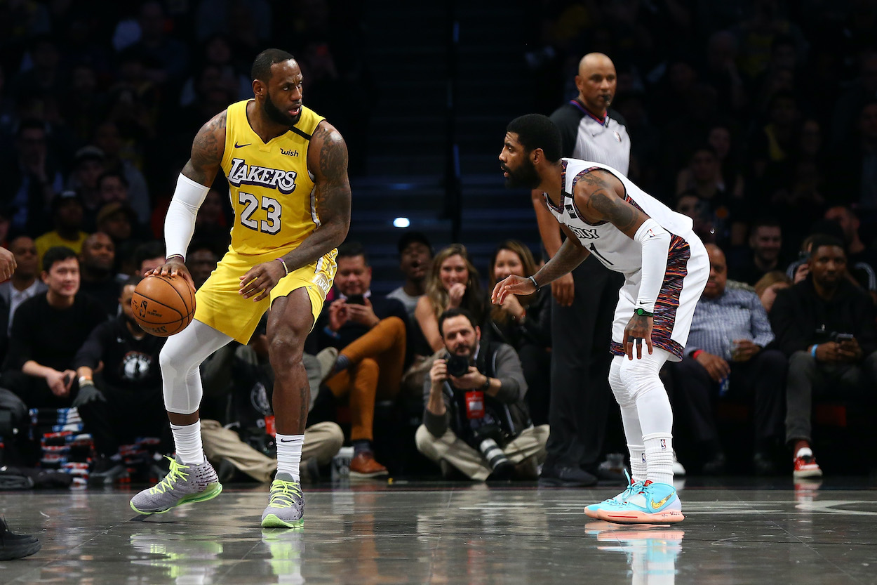LA Lakers forward LeBron James backs down Brooklyn Nets guard Kyrie Irving