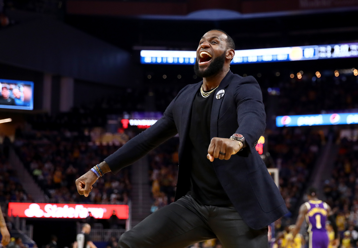 LeBron James celebrates a Lakers dunk from the bench.