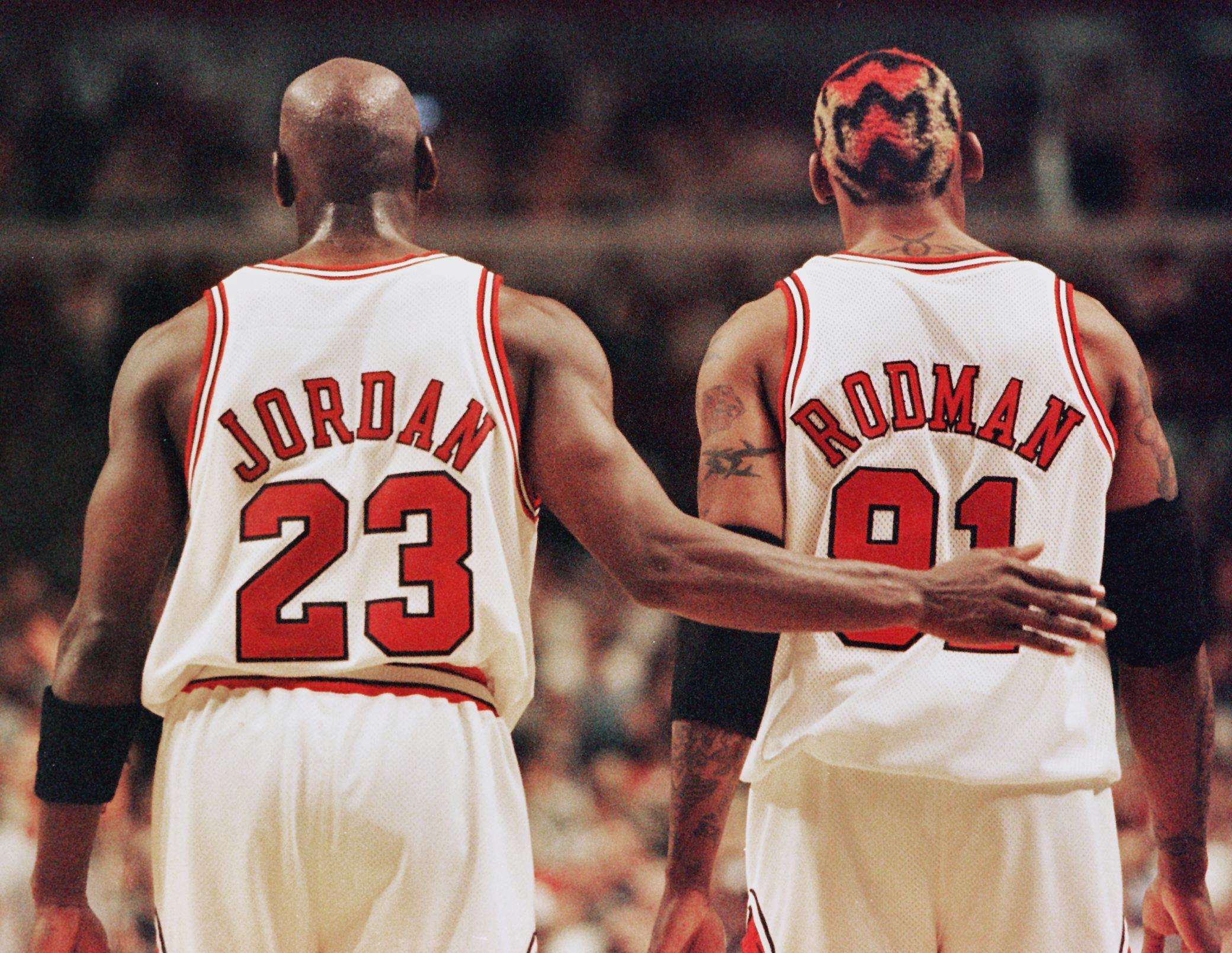 Michael Jordan (L) pats Dennis Rodman, both of the Chicago Bulls, on the back after Rodman was called for a technical foul