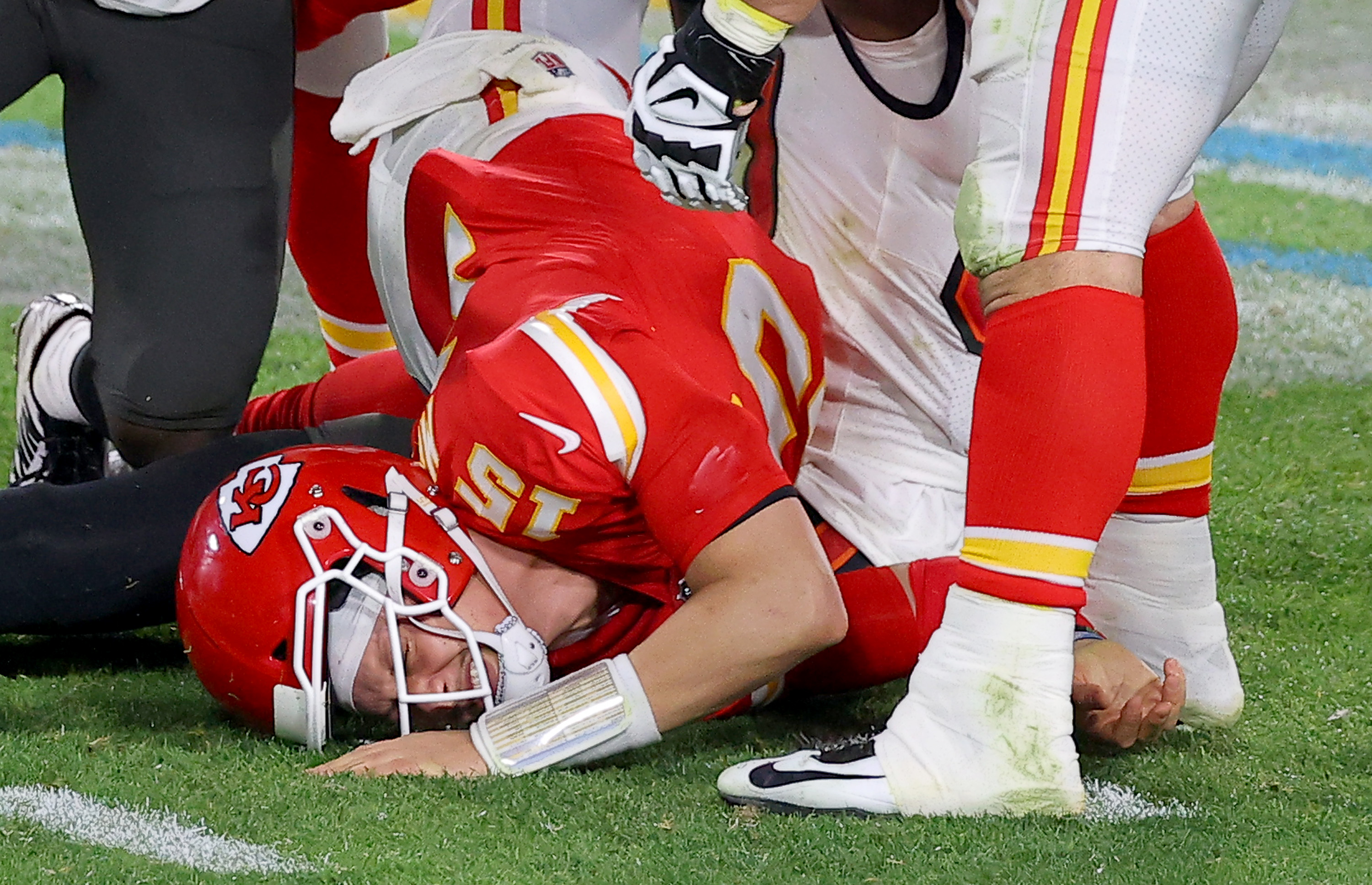 Quarterback Patrick Mahomes of the Kansas City Chiefs lies on the field after being hit