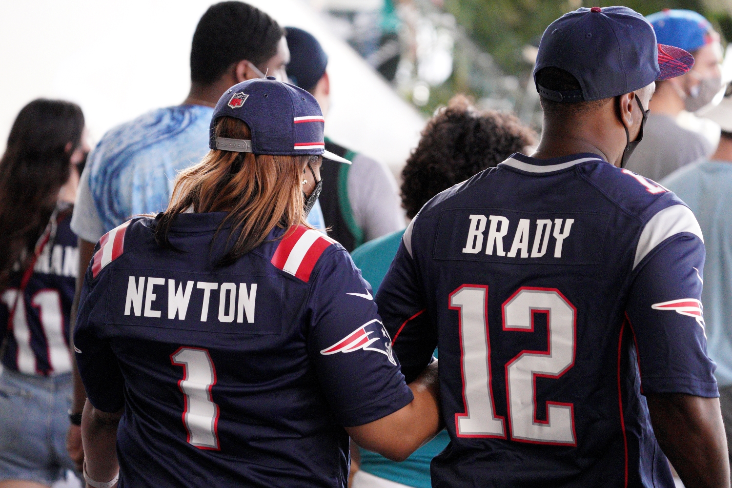 Patriots fans wearing Tom Brady and Cam Newton jerseys walk together during a game at Hard Rock Stadium.
