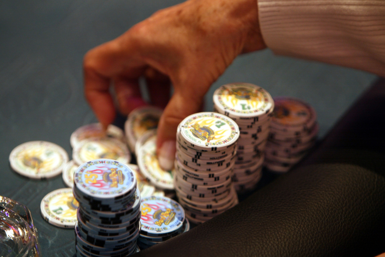 A poker player prepares to throw some chips into the pot