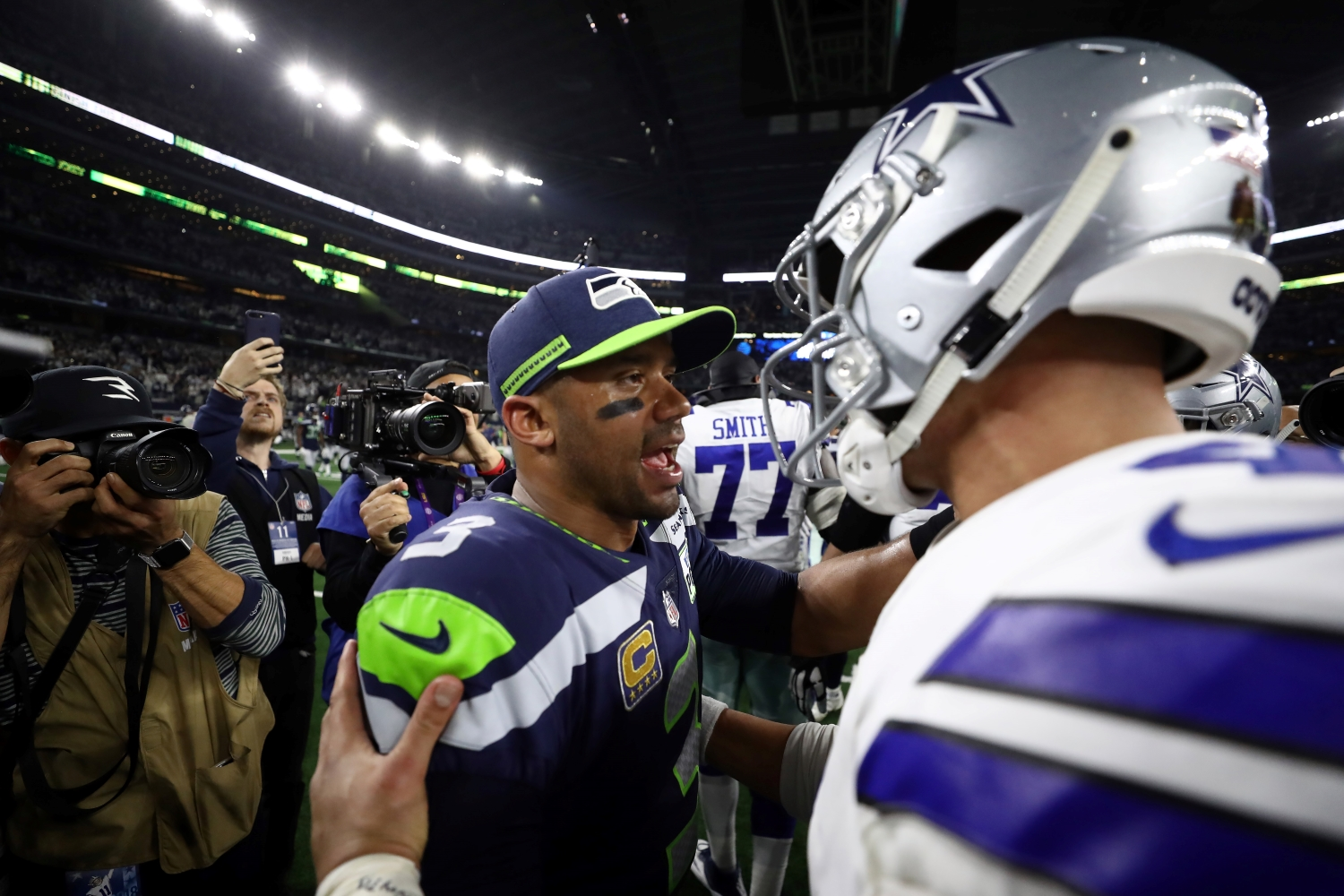 Dak Prescott of the Dallas Cowboys talks with Russell Wilson of the Seattle Seahawks after the Cowboys defeated the Seahawks 24-22 in the Wild Card Round.