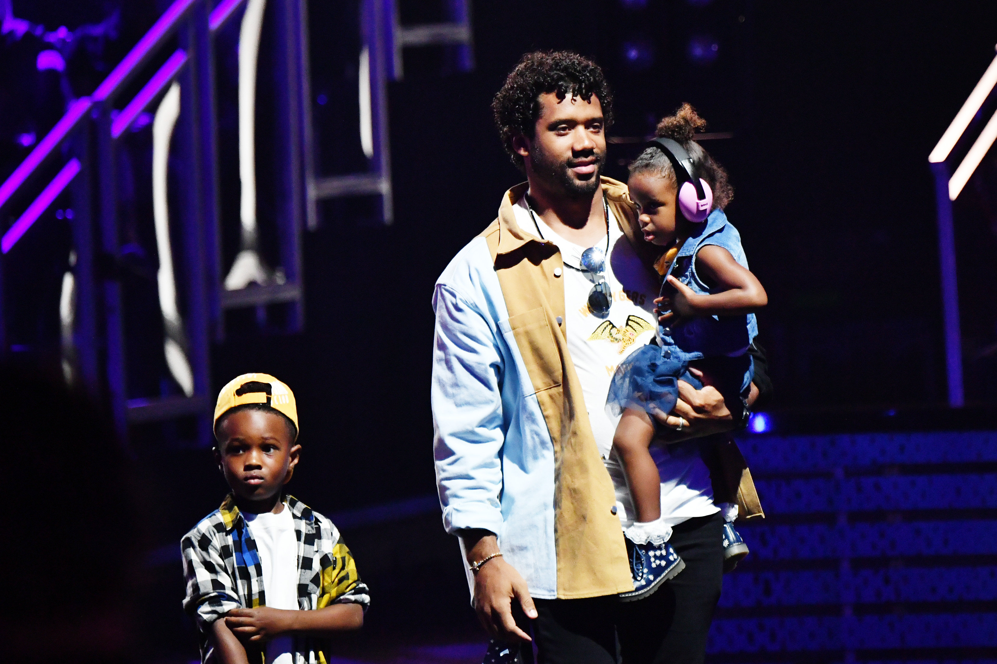 Russell Wilson walks out on to a stage with his kids