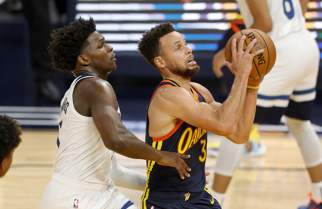 Warriors star Stephen Curry gets by Timberwolves rookie Anthony Edwards.