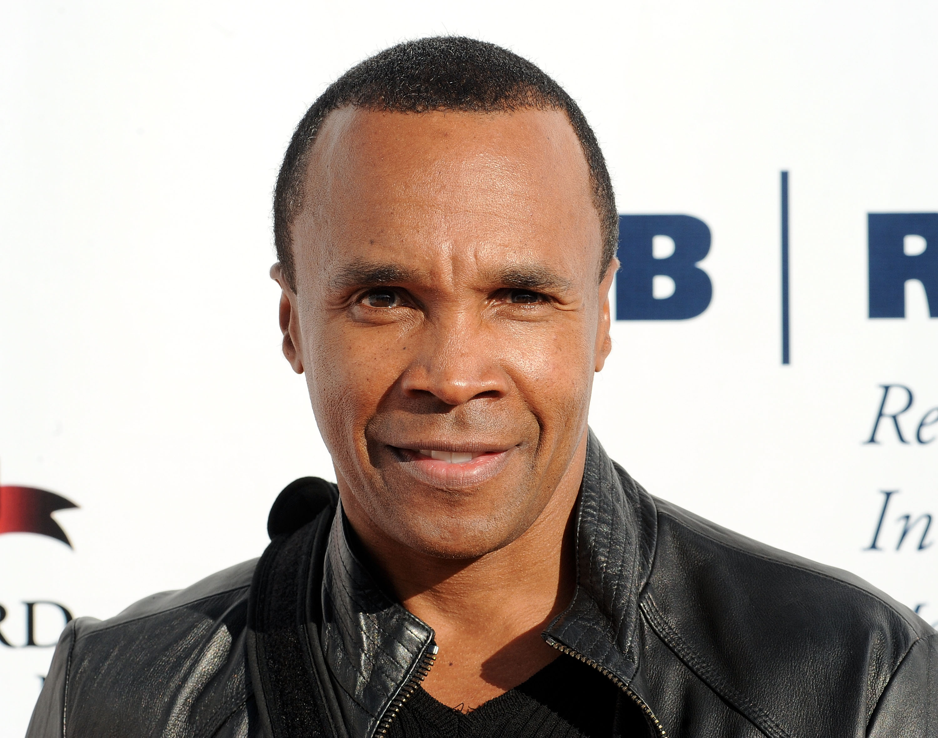 Sugar Ray Leonard smiles for a photo at a charity event