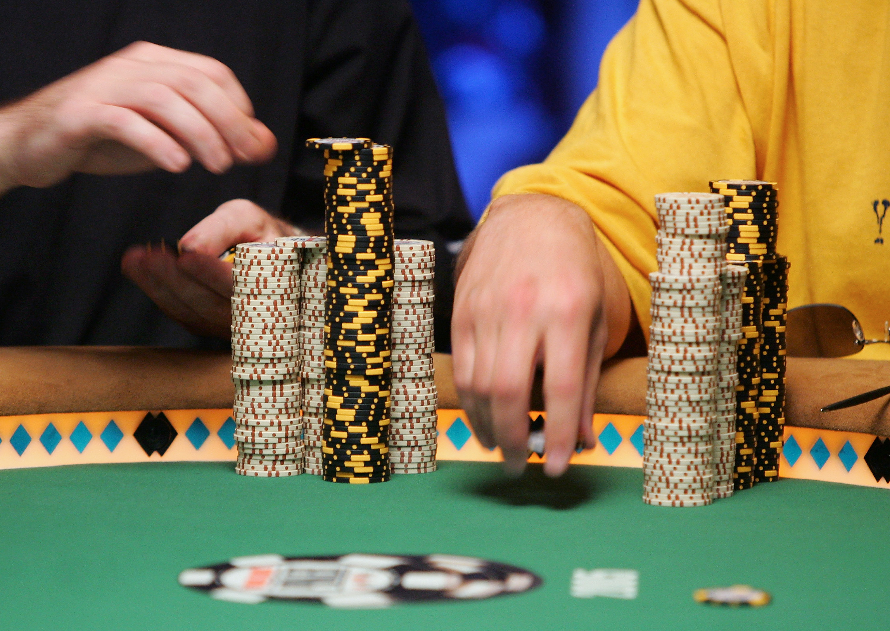 A player reaches for their chips during a game of poker