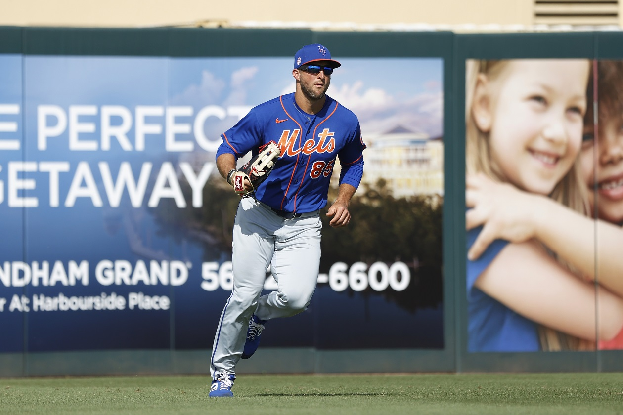 Tim Tebow walks onto the field during a Mets spring training game.