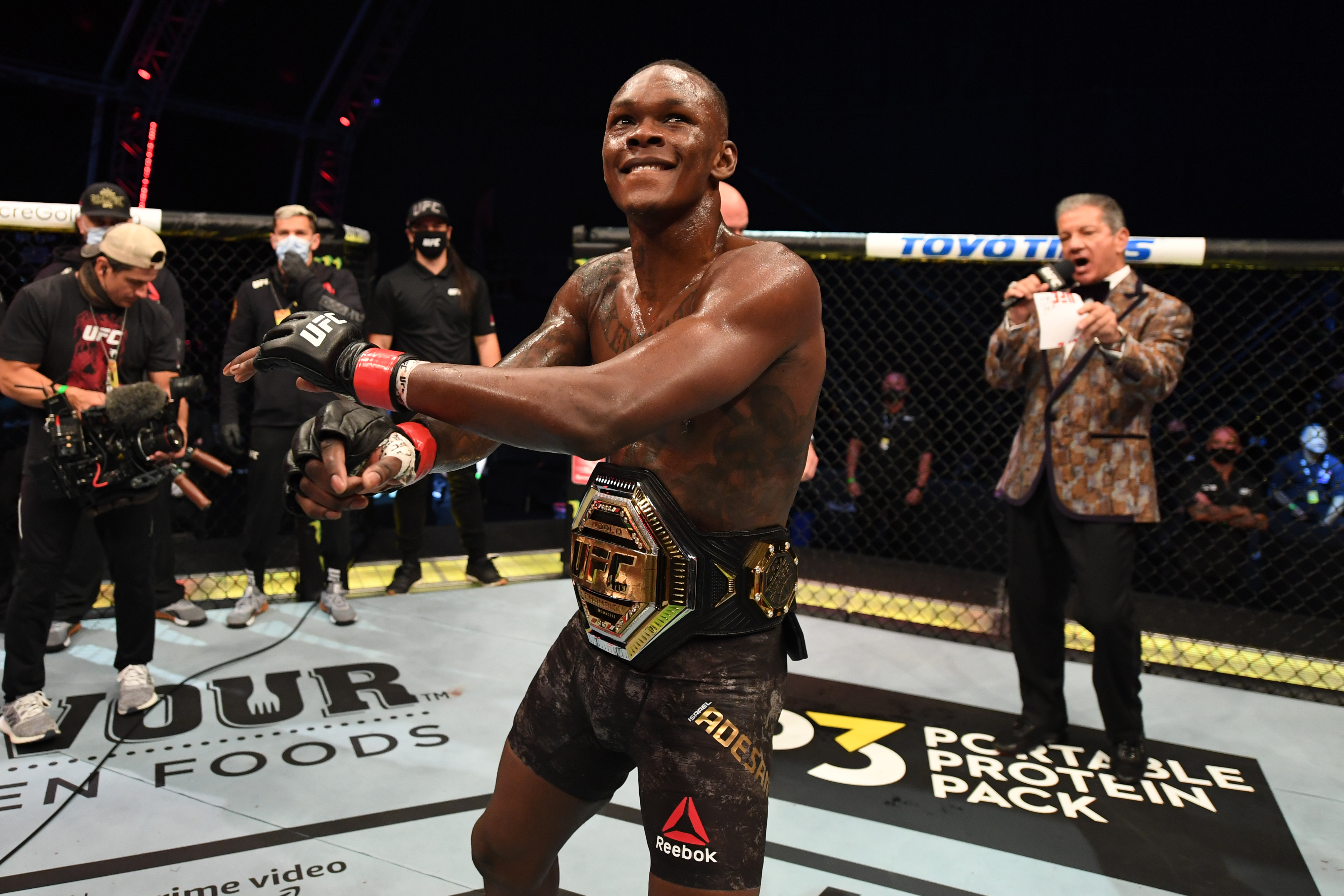 Israel Adesanya celebrates after defeating Paulo Costa of Brazil in their middleweight championship bout