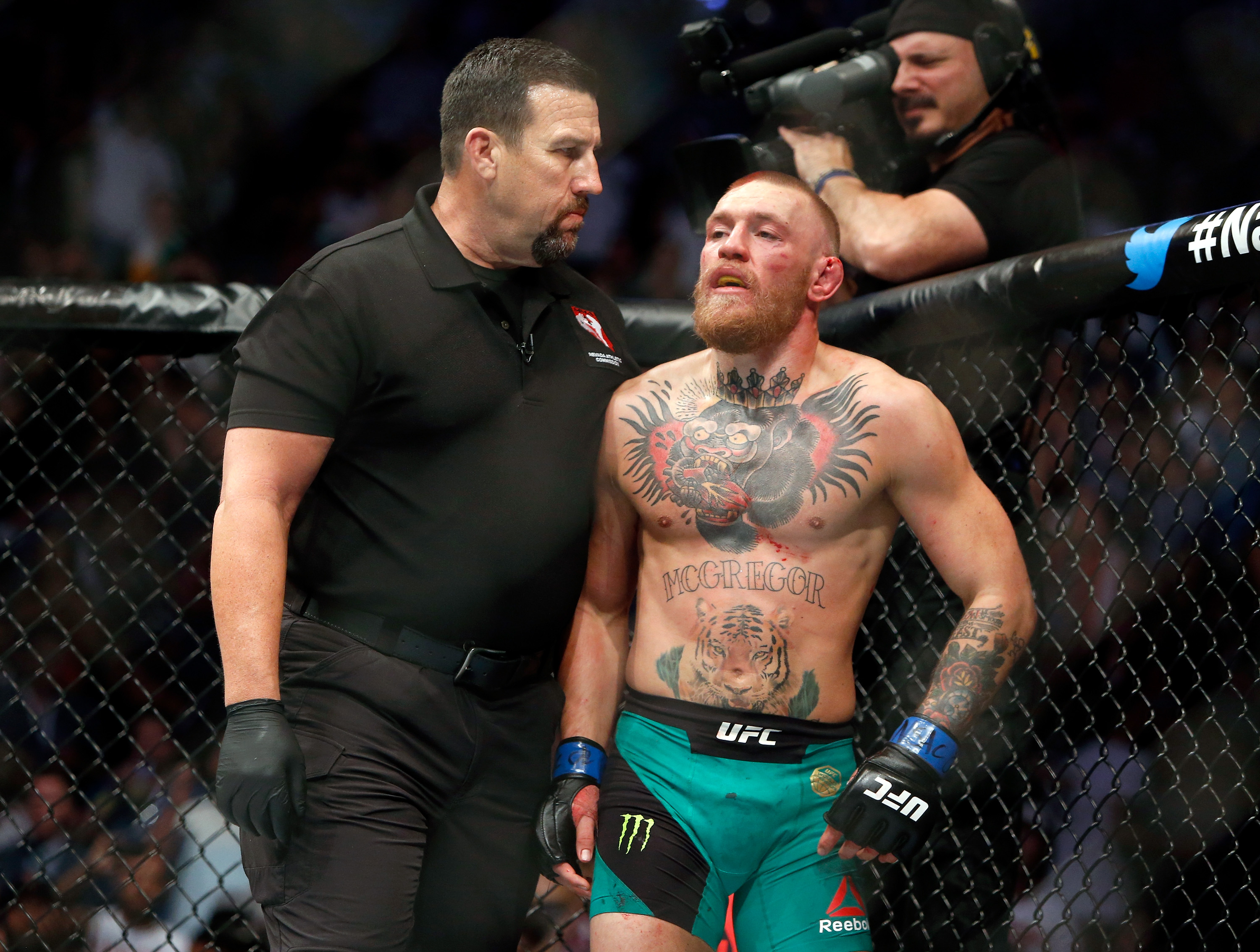 Referee John McCarthy (L) makes sure Conor McGregor goes back to his corner in 2016