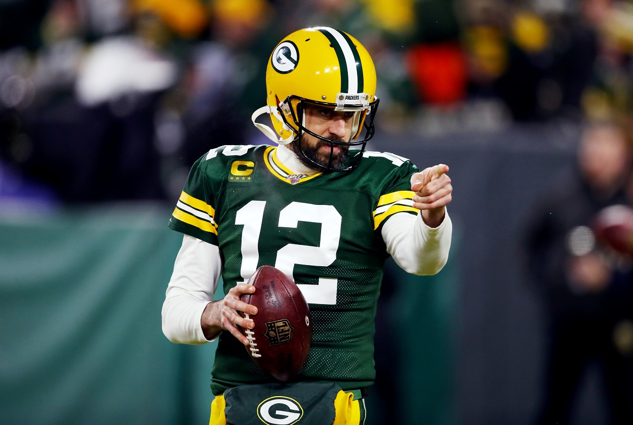 Green Bay Packers quarterback Aaron Rodgers gestures to a team during a play.