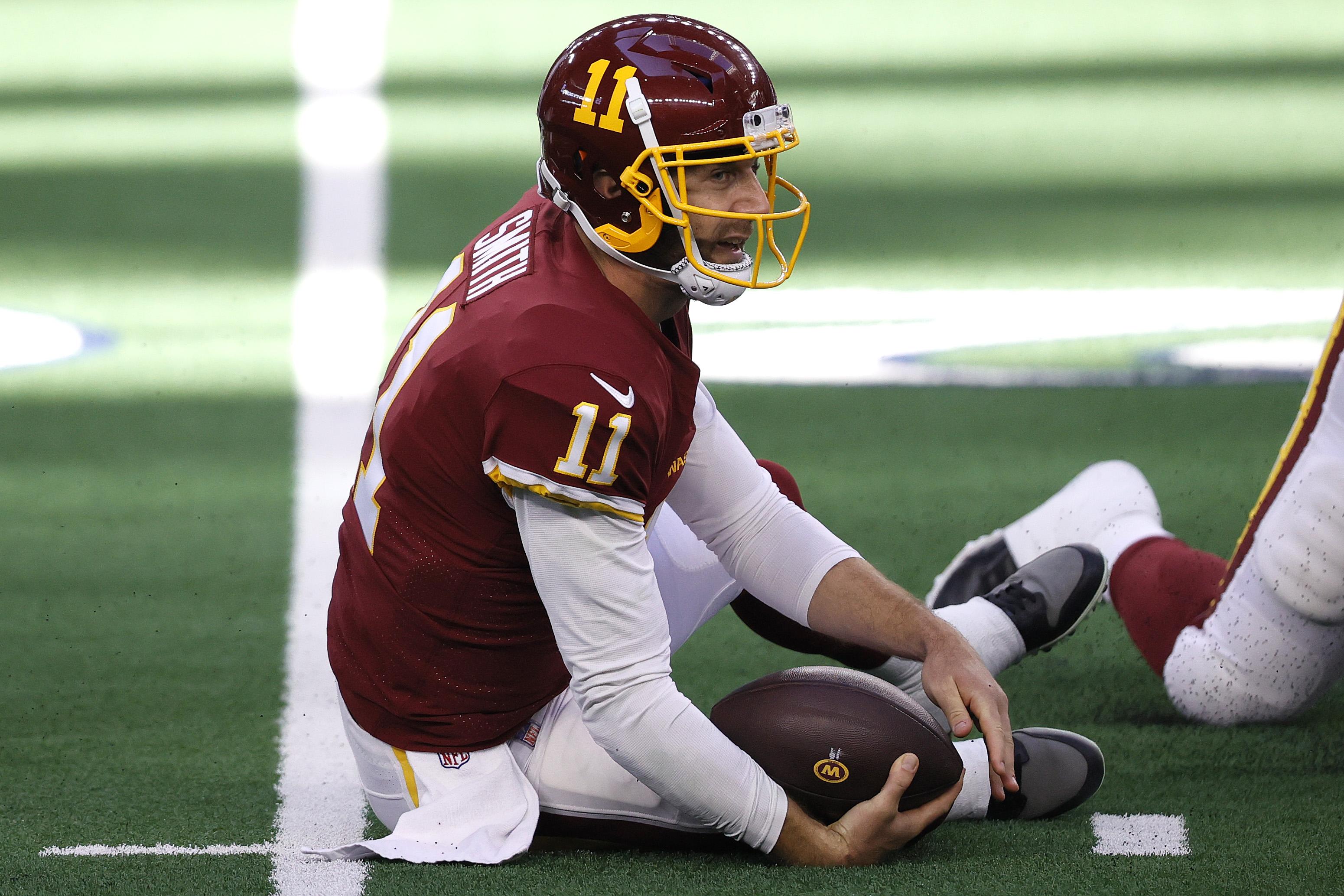 Alex Smith of the Washington Football Team sits on the field
