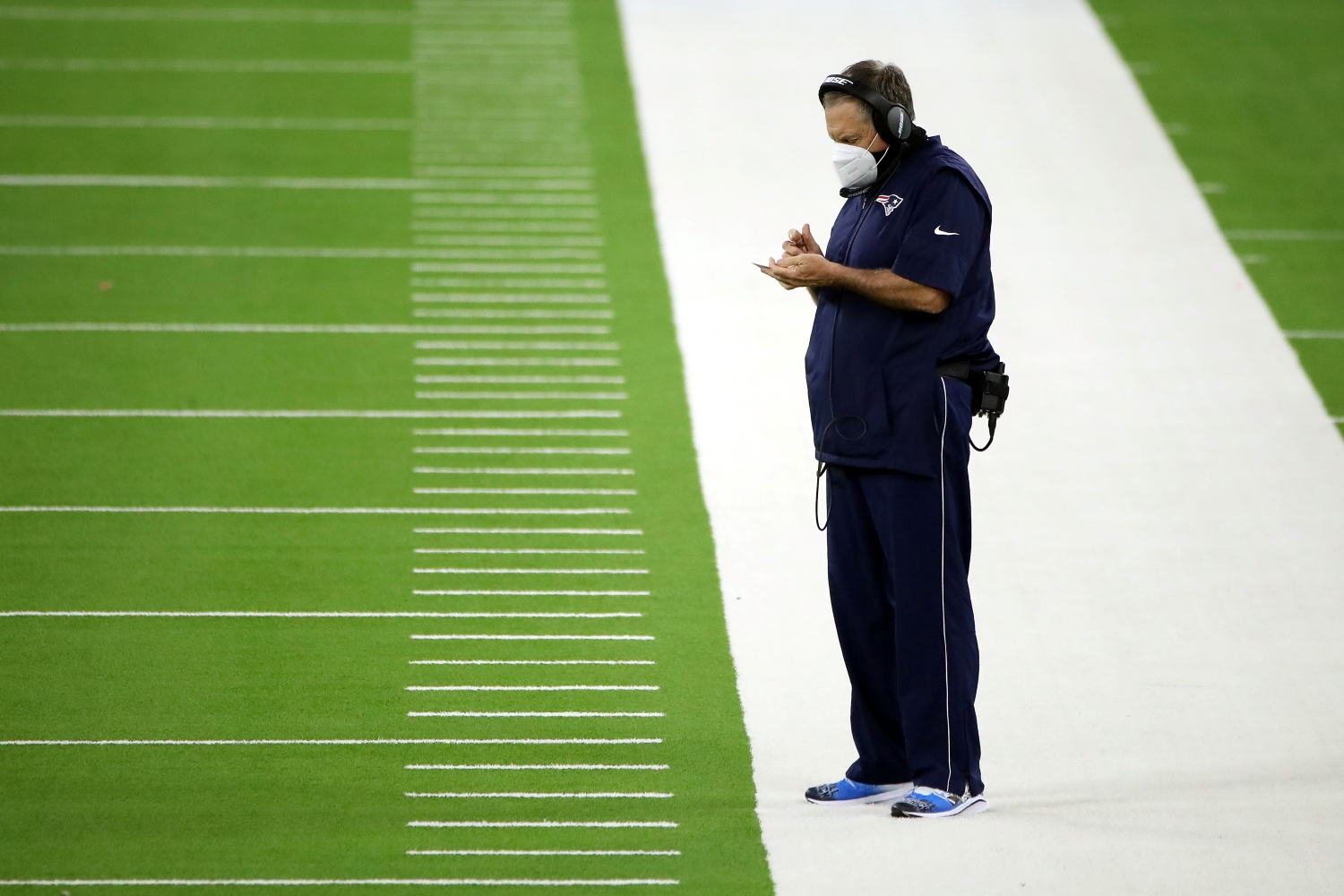 Patriots head coach Bill Belichick stands on the sidelines during the first quarter of a 2020 game against the LA Rams.
