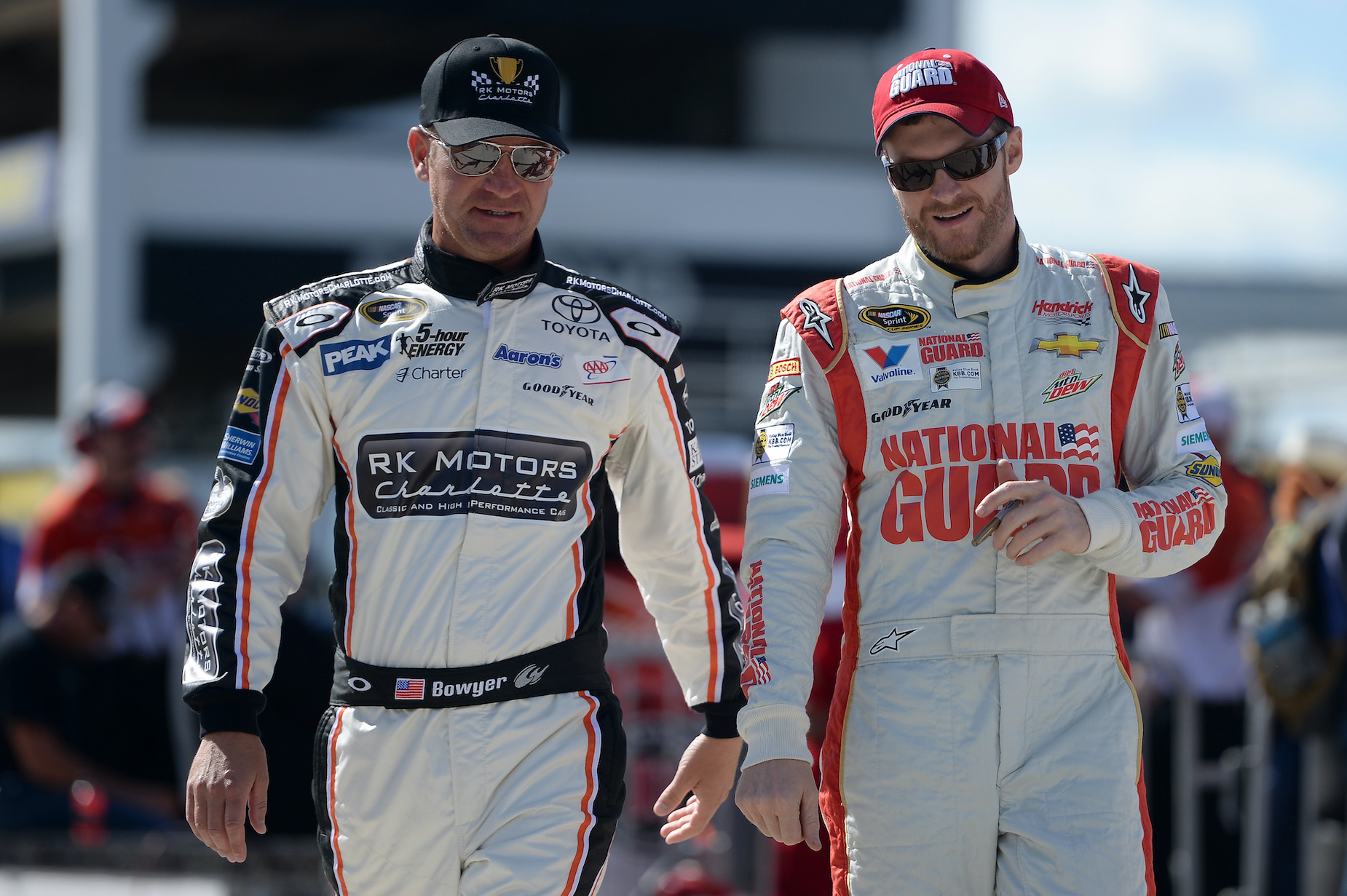 NASCAR Drivers Clint Bowyer (L) and Dale Earnhardt Jr. (R) walk together at Pocono Raceway on June 6, 2014