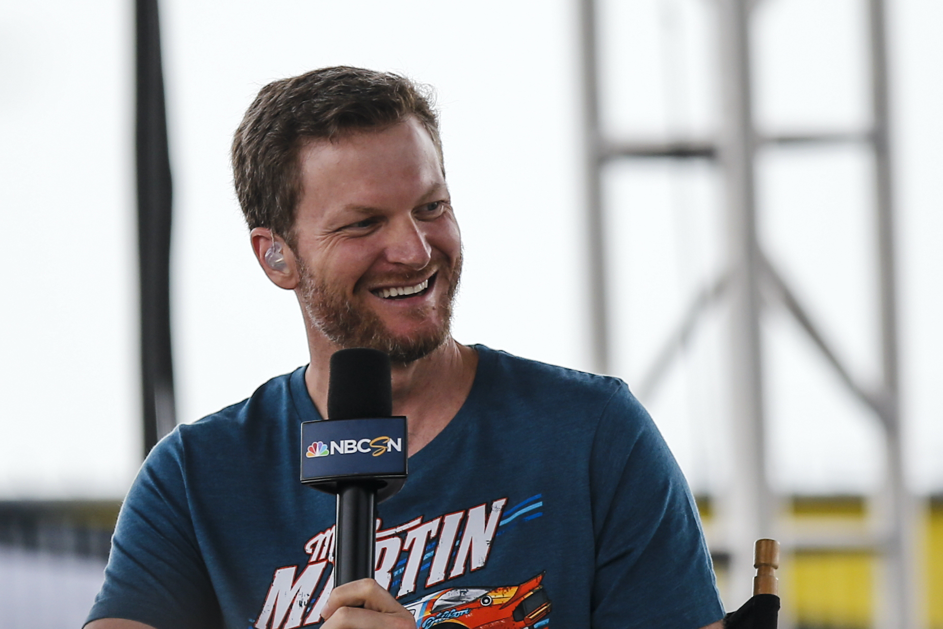 NASCAR star Dale Earnhardt Jr. smiles while holding a microphone