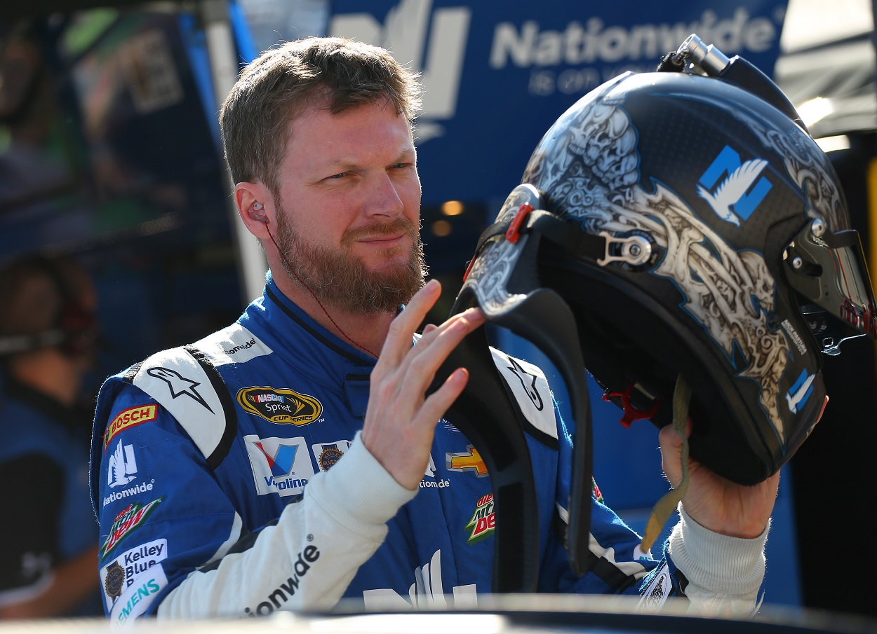 Dale Earnhardt Jr. puts on his helmet for a NASCAR race.