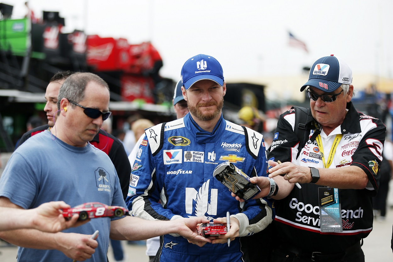 Dale Earnhardt Jr. signs autographs for fans during a practice run for NASCAR's Sprint Cup Series race