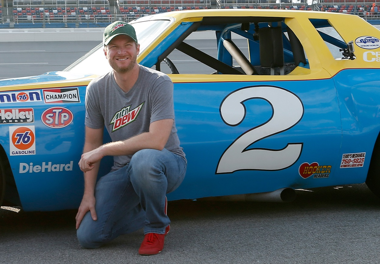 Dale Earnhardt Jr. pose by the his father's old NASCAR car that Talladega Superspeedway presented to him.