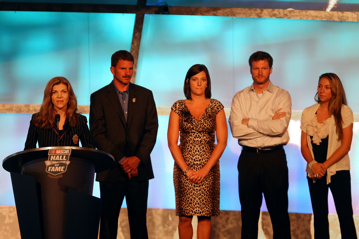 Dale Earnhardt Jr. and his siblings stand behind their stepmother Teresa Earnhardt during their father's NASCAR Hall of Fame induction.