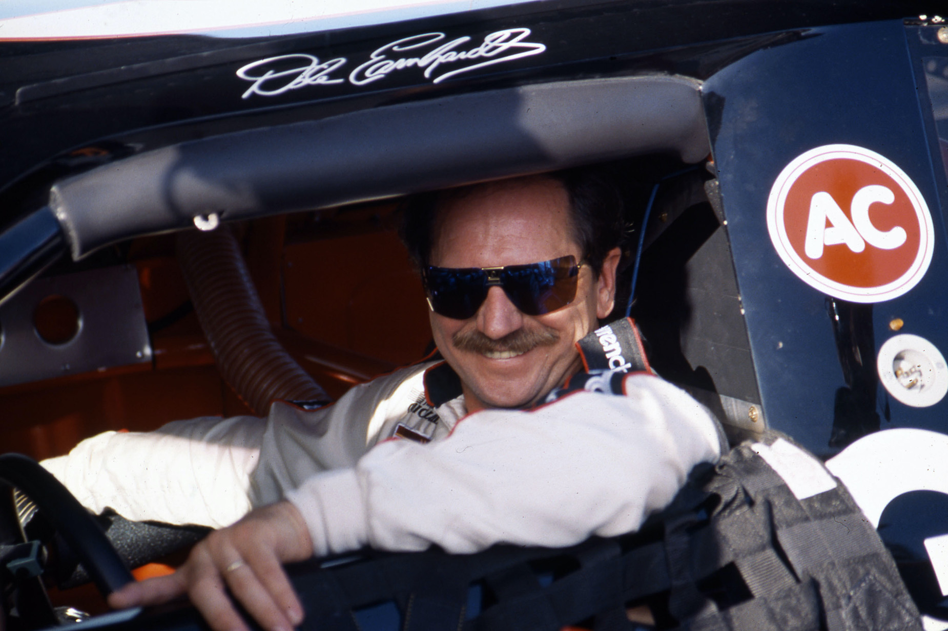 NASCAR legend Dale Earnhardt, showing his signature mustache, sits in the driver's seat.