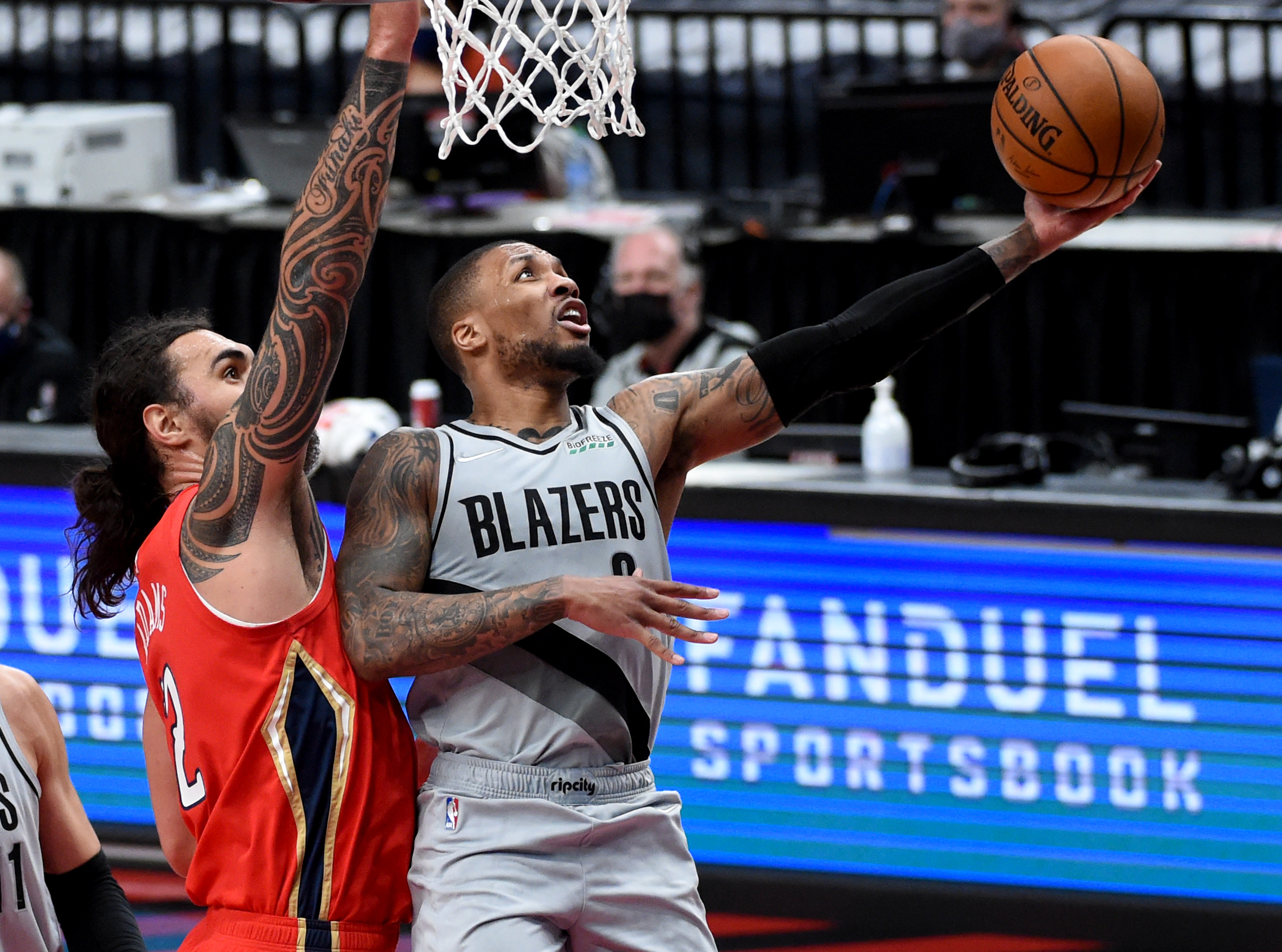 Damian Lillard of the Portland Trail Blazers drives to the basket on Steven Adams of the New Orleans Pelicans