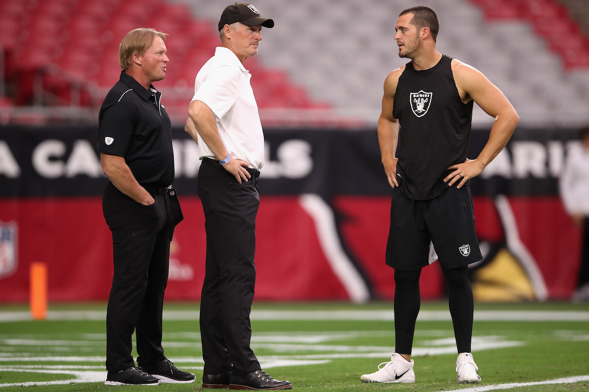 Las Vegas coach Jon Gruden (L) speaks with Mike Mayock (M) and Derek Carr (R)