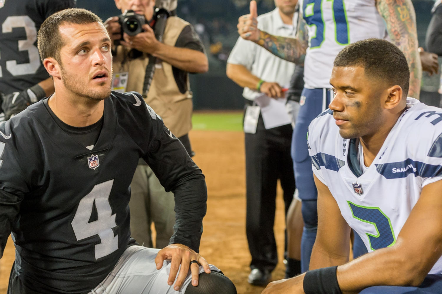 Derek Carr and Russell Wilson kneel in prayer following a game between the Raiders and the Seahawks in August 2017.