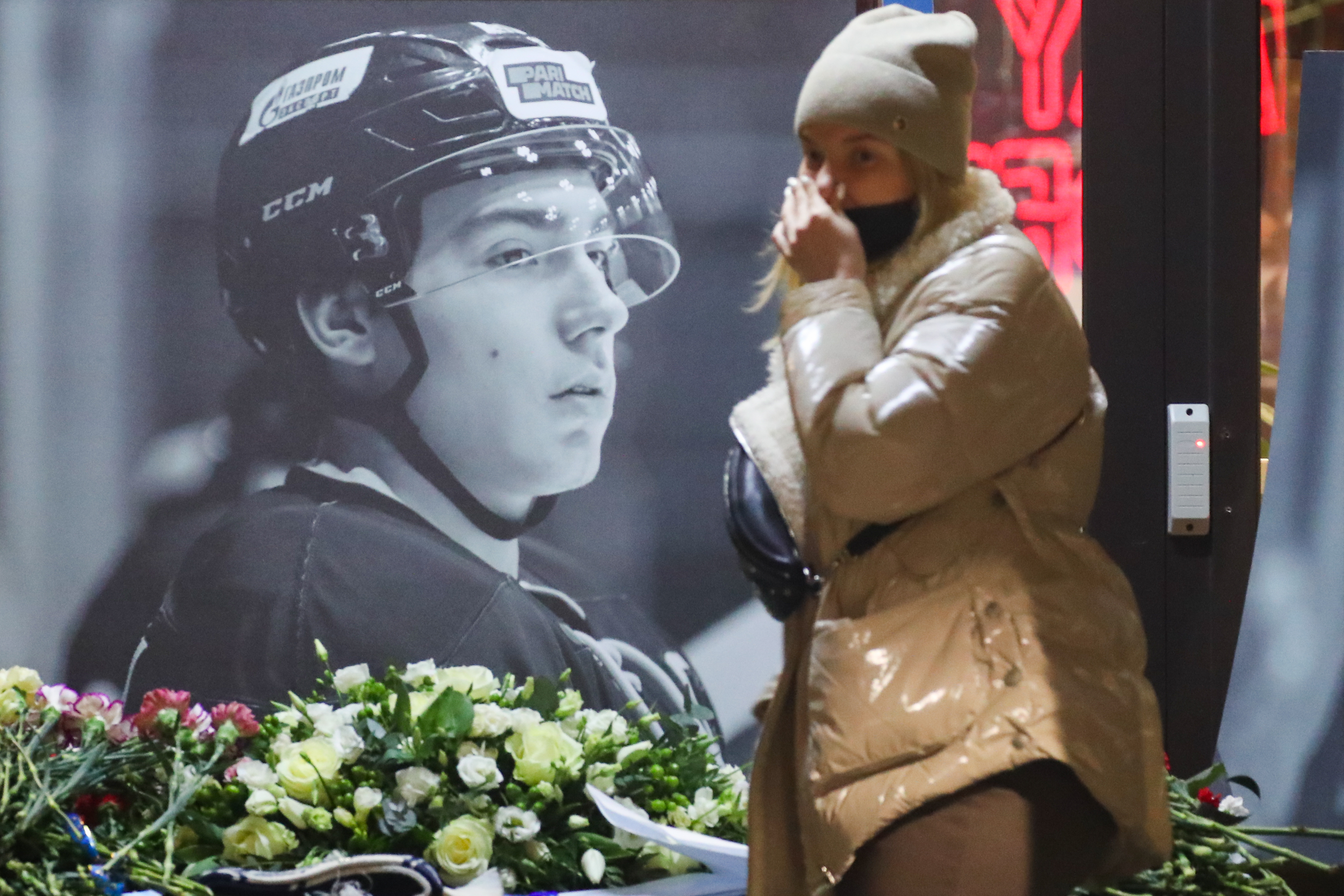 A woman stands before a makeshift memorial set up outside the Yubileyny Sports Palace in tribute to the late Junior Hockey League player Timur Faizutdinov